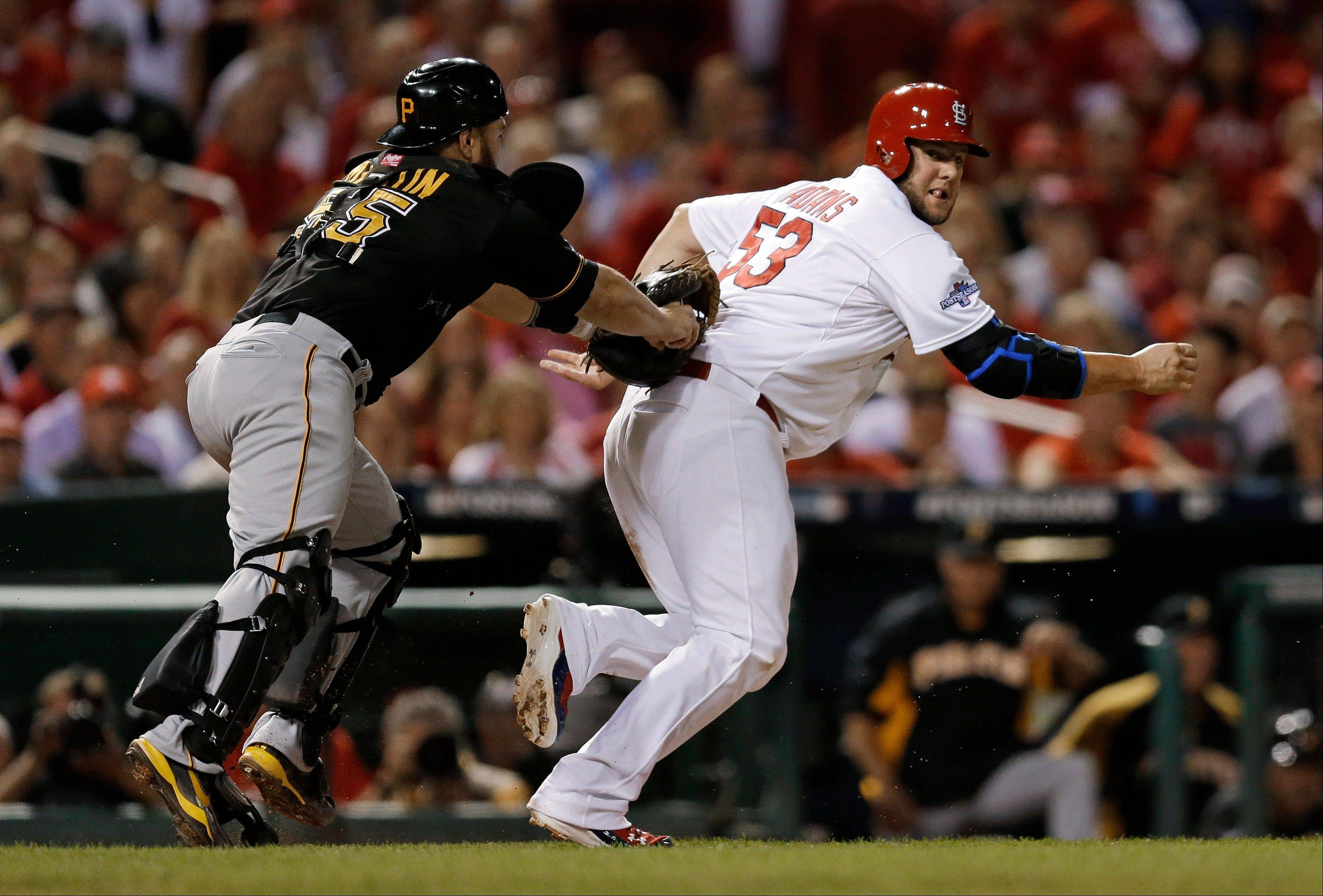 The Cardinals' Matt Adams is tagged out by the Pirates' Russell Martin in the fourth inning of Game 5 in St. Louis. Adams was caught between third and home on a ground ball by Jon Jay.