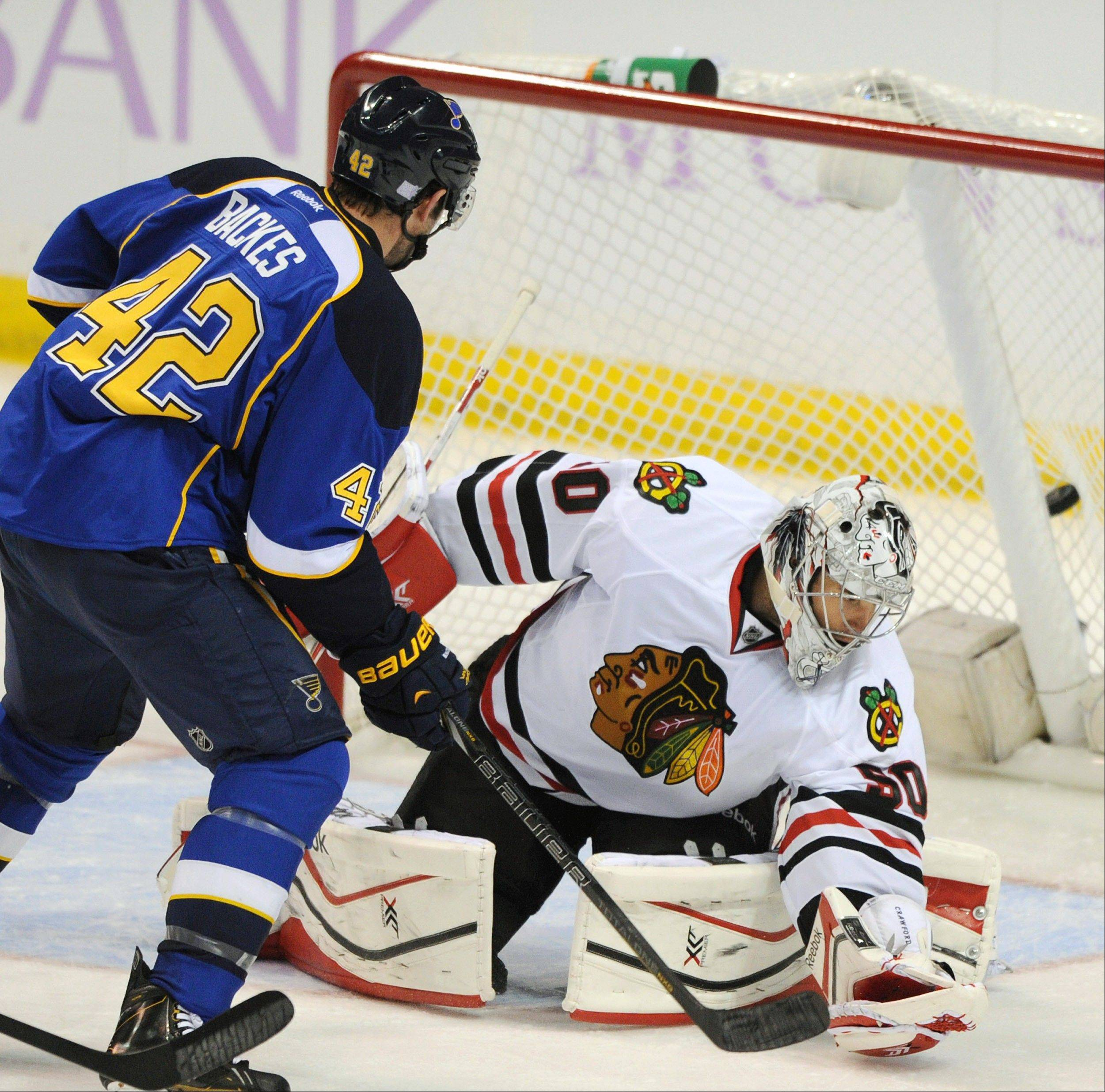 Chicago Blackhawks' goalie Corey Crawford, right, is scored on by St. Louis Blues' David Backes (42) during the second period of an NHL hockey game Wednesday, Oct. 9, 2013, in St. Louis.