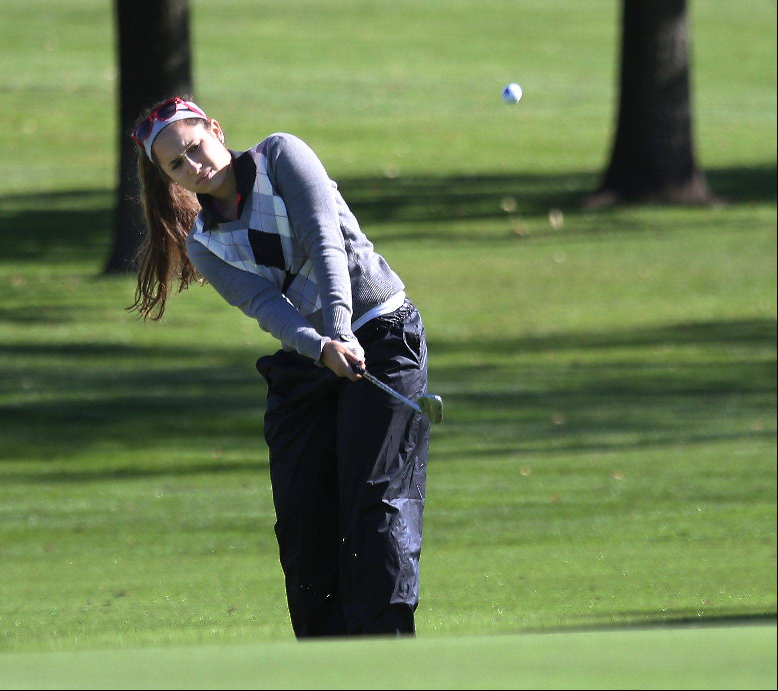 Mundelein golfer Cristina Loverde hits a shot onto the green on the first hole during the Class AA Carmel girls golf regional Wednesday at Bonnie Brook.