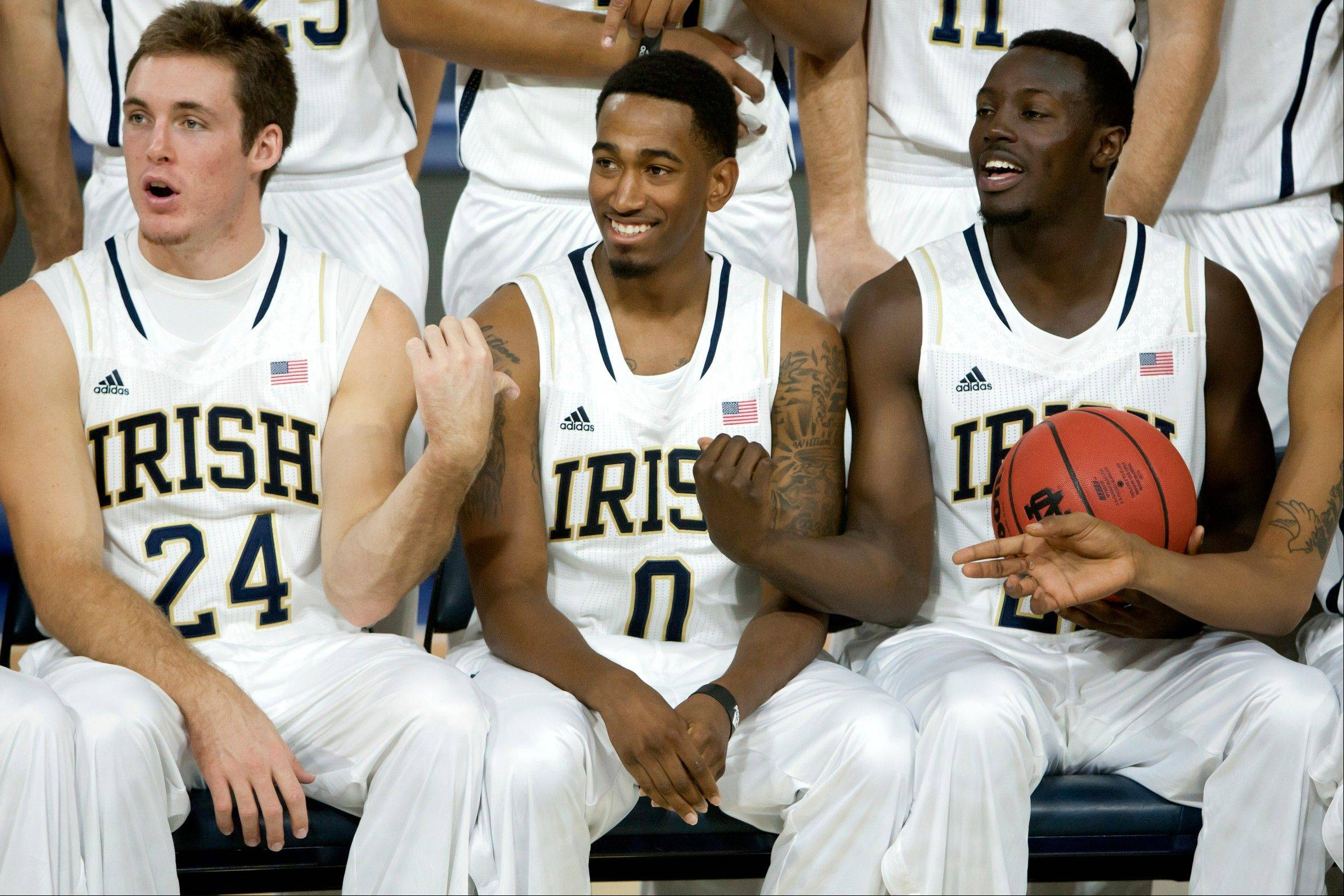Notre Dame's Pat Connaughton, left, and Jerian Grant ask their sports information director to give Eric Atkins, center, a basketball for their official photograph during team's media day Wednesday in South Bend, Ind.