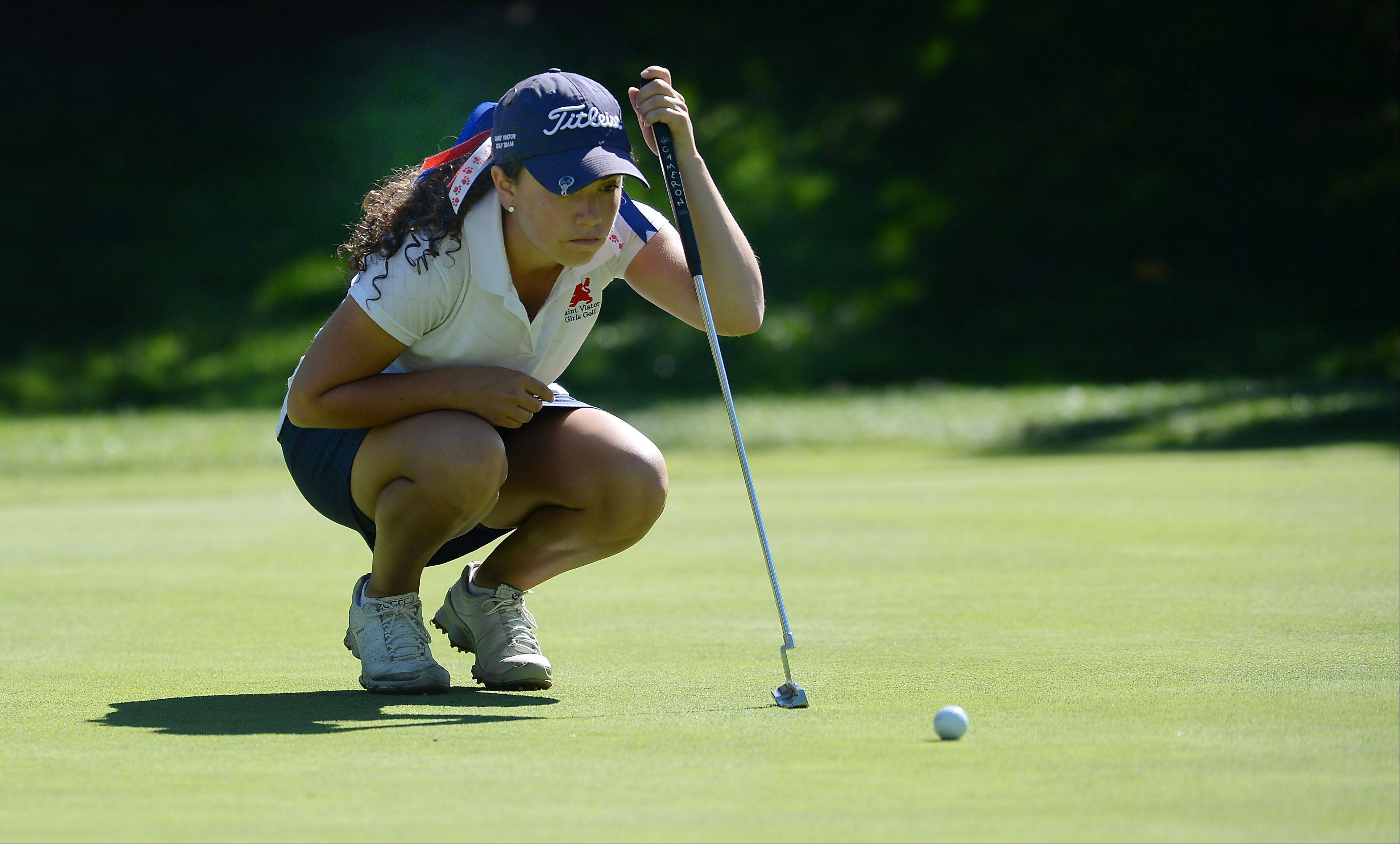 St. Viator's Dana Gattone eyes her ball for a putt on No. 18 in the girls golf regional at Mt. Prospect Golf Club on Wednesday.