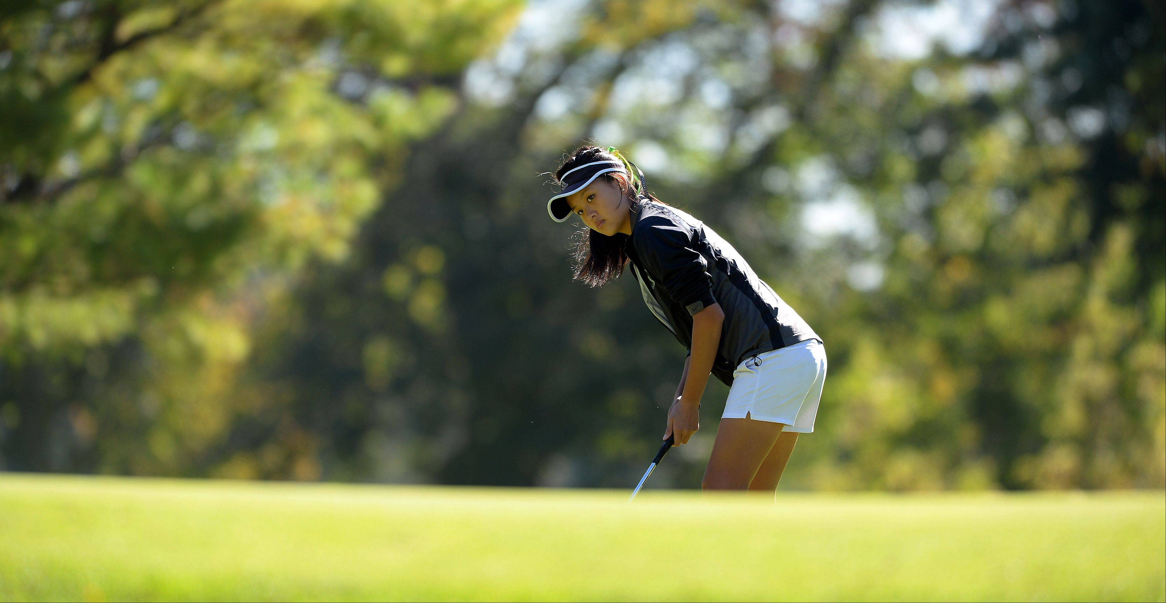 Dorothy Feng of Fremd High School watches her ball as she putts on the first hole in the girls golf regional at Mt. Prospect Golf Club on Wednesday.