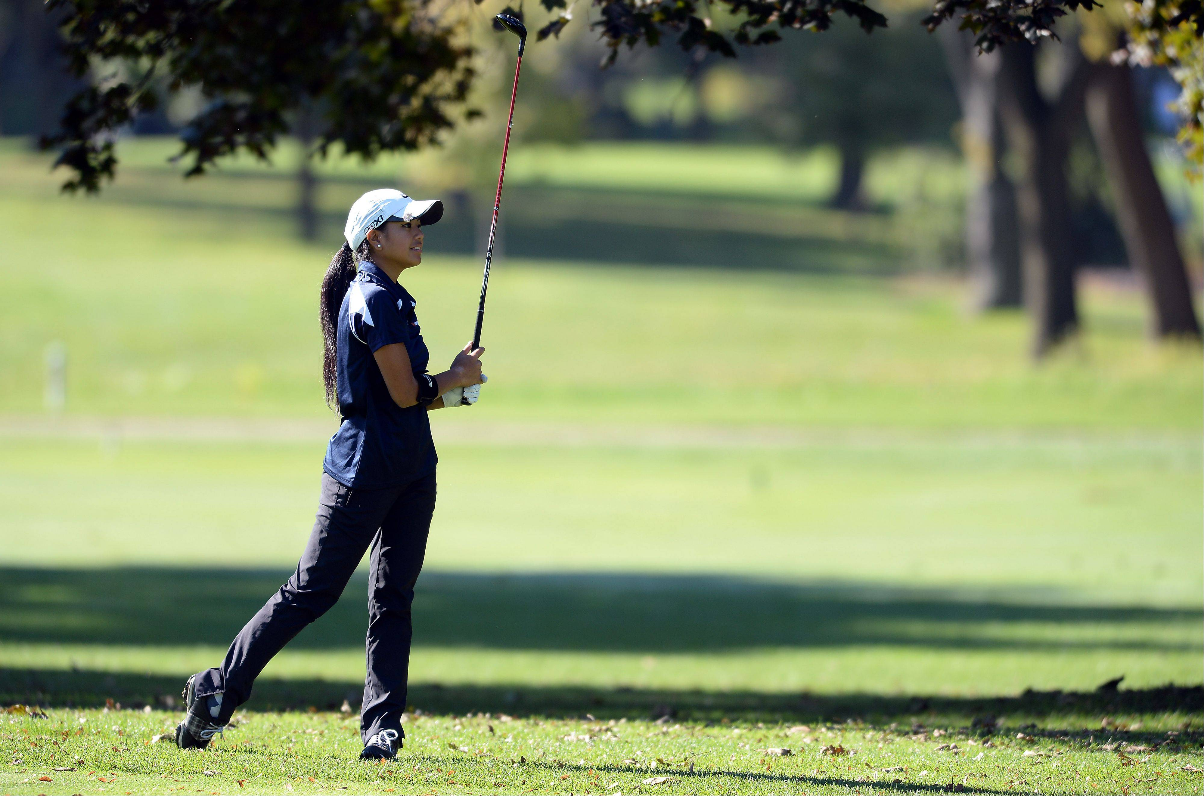 Amber Guiao of Buffalo Grove High School smiles as she drives her ball down the fairway on the first hole in the girls golf regional at Mt. Prospect Golf Club on Wednesday.