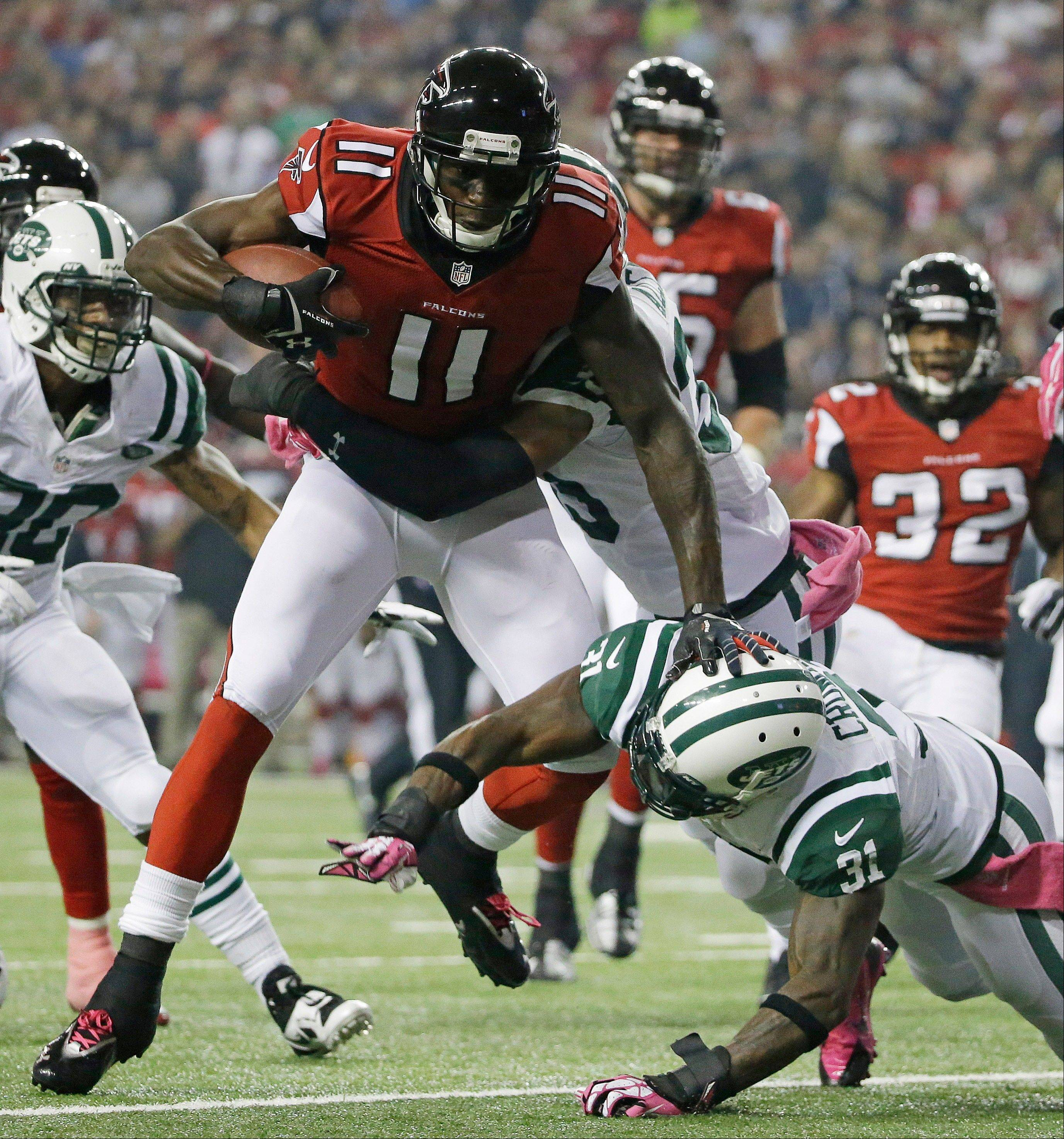 Atlanta Falcons wide receiver Julio Jones (11) is hit by New York Jets free safety Antonio Allen (39) and New York Jets cornerback Antonio Cromartie (31) during the first half of an NFL football game, Monday, Oct. 7, 2013, in Atlanta.