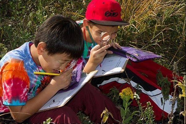 Two fourth-grade citizen scientists have fun learning and using their skills on the prairie with Citizens for Conservation.