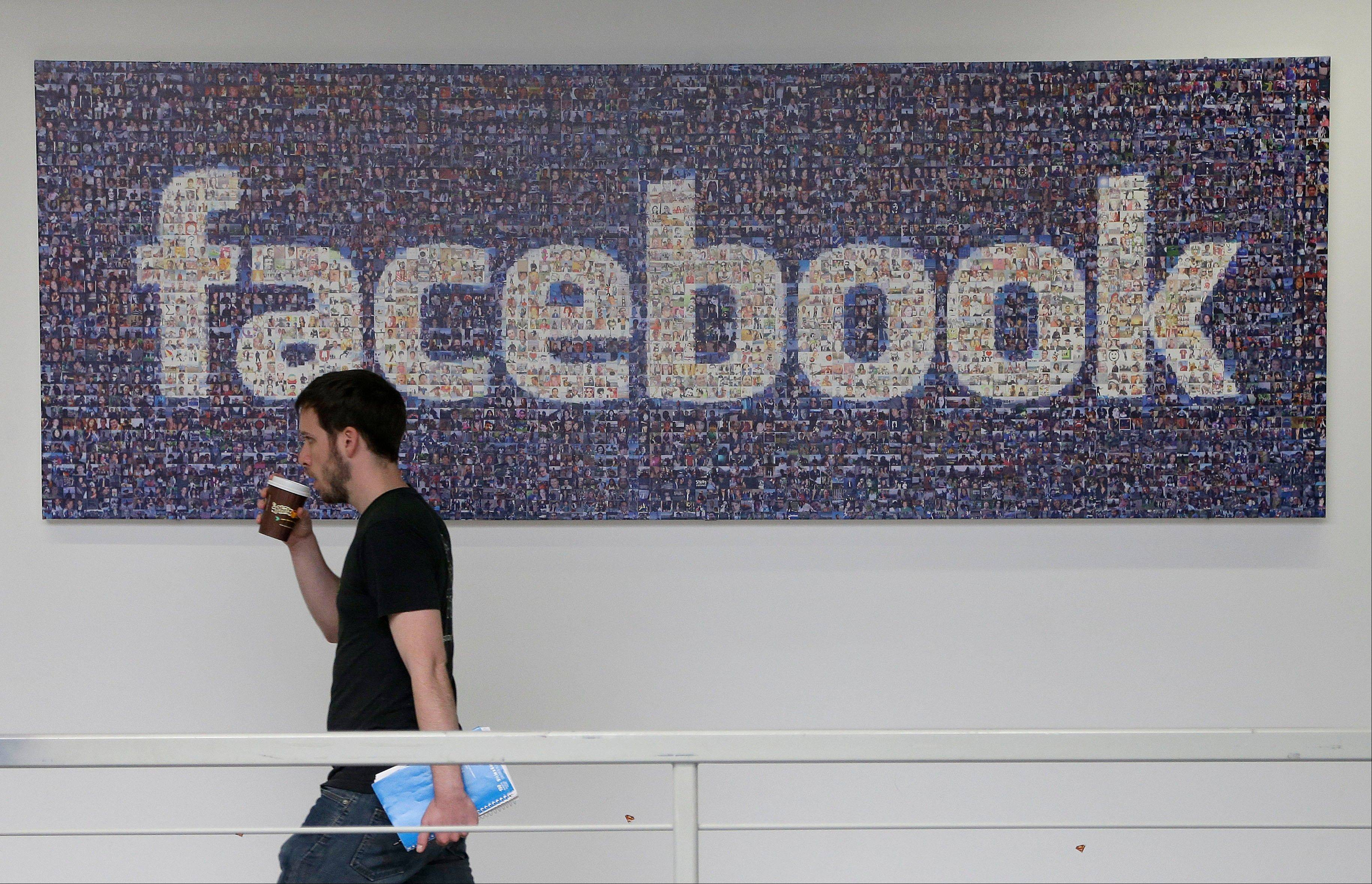 Associated Press/March 15, 2013 A Facebook employee walks past a sign at Facebook headquarters in Menlo Park, Calif.