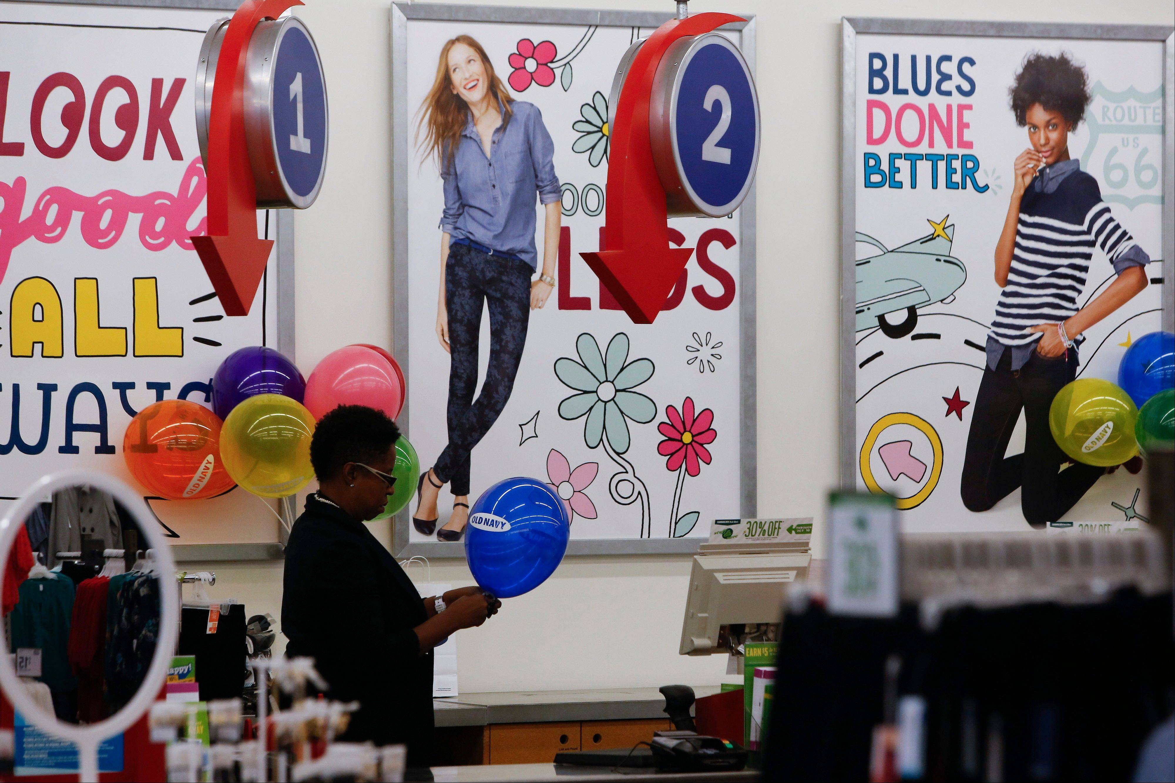 An employee fills a balloon Tuesday at an Old Navy Inc. store in Santa Monica, Calif.