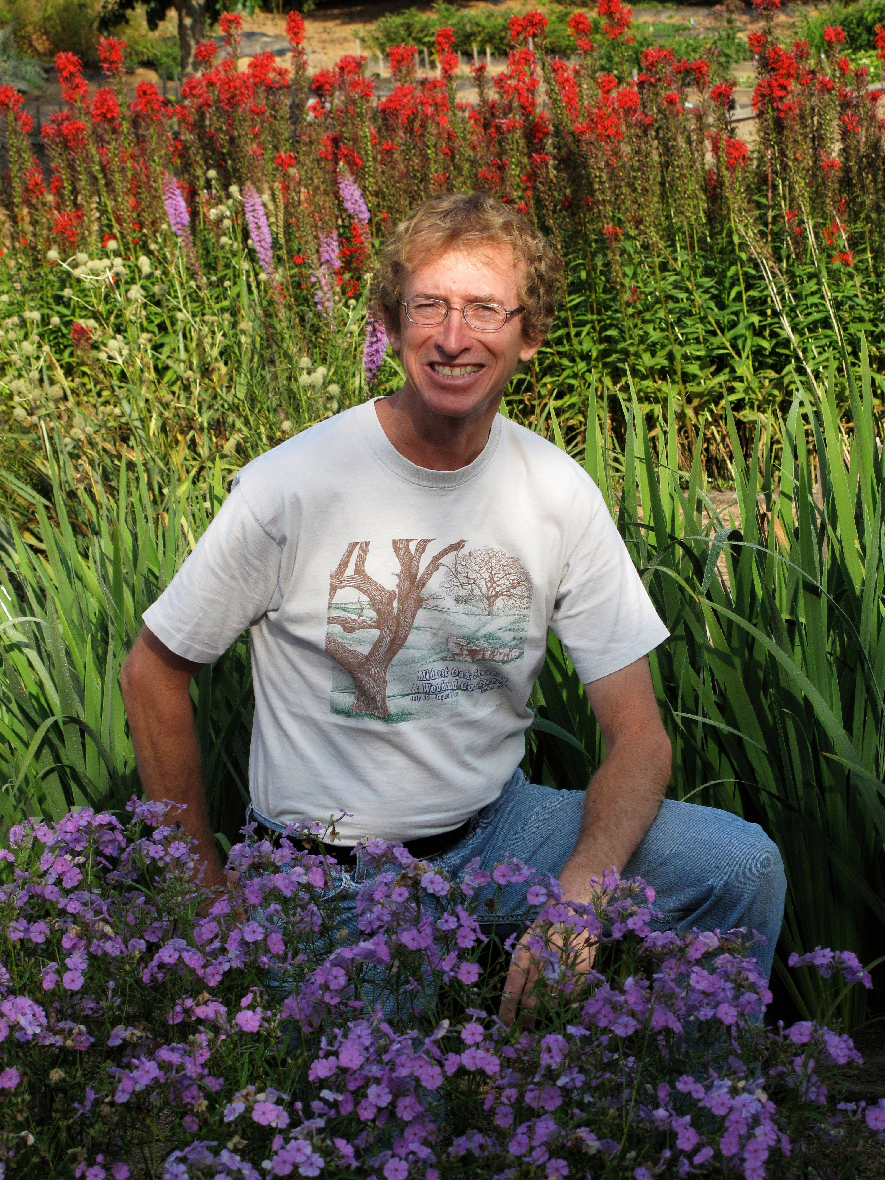 Bill Carter, president of Prairie Moon Nursery, poses amid an assortment of prairie flowers sown in a nearby farmyard near Winona, Minn. Many of these seeded perennials need two or three years to reach blooming size but really take off once established.