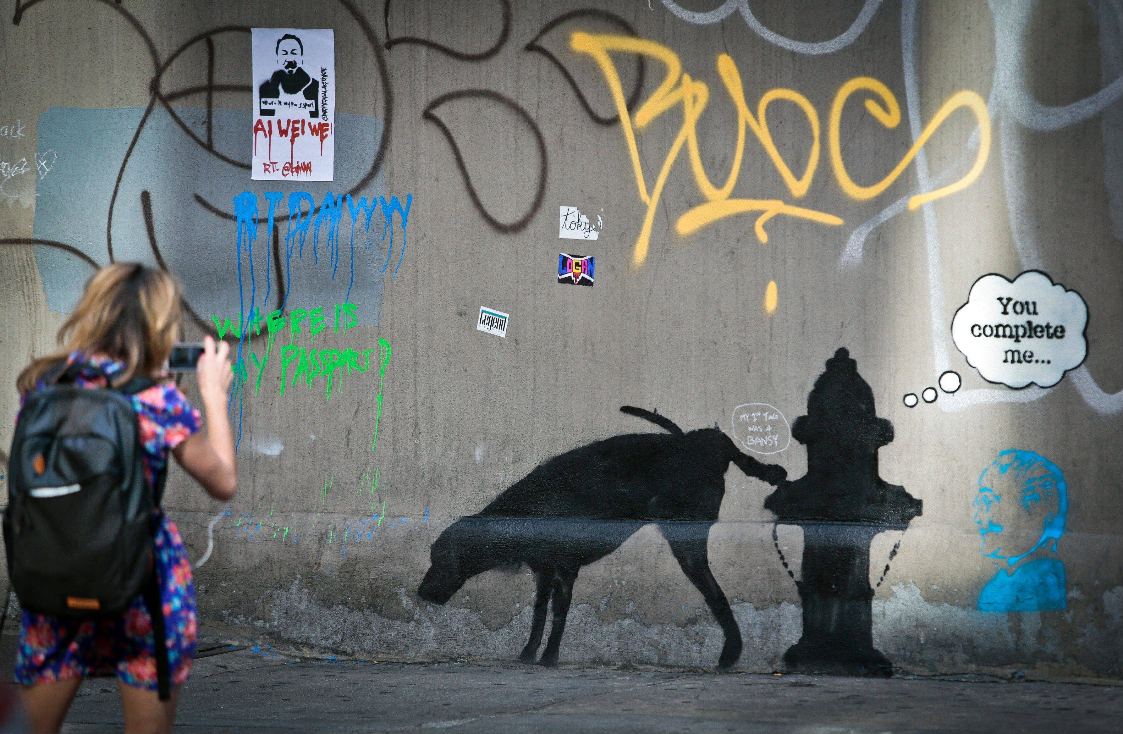 Graffiti by the secretive British artist Banksy, featuring a dog and a fire plug, draws attention on 24th Street, near Sixth Avenue in New York, on Friday. Banksy graffiti is turning up on the streets of the city and all over social media.
