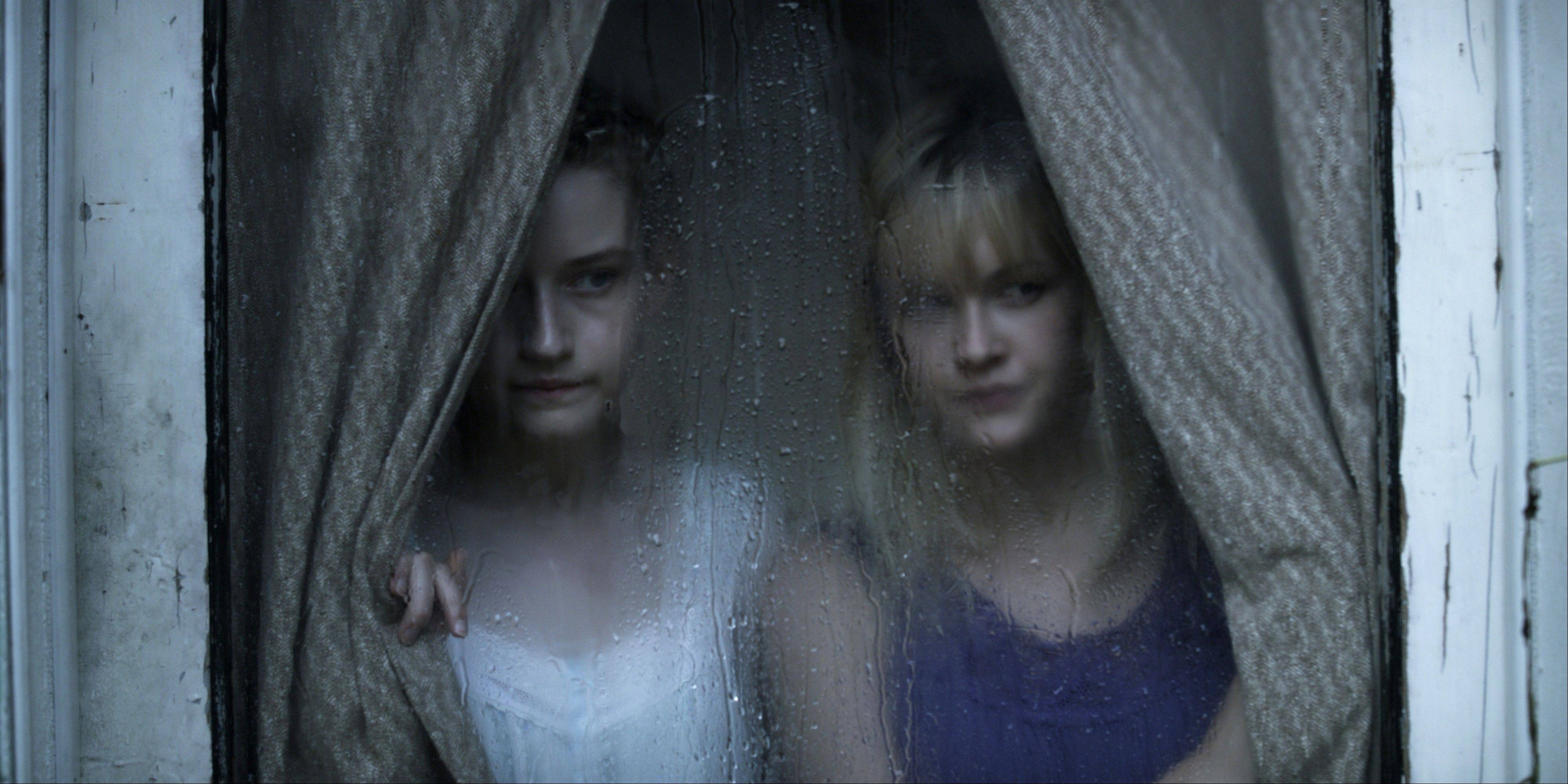 "Julia Garner, left, and Ambyr Childers play the daughters of a mysterious man who keeps to himself in Jim Mickle's gothic drama ""We Are What We Are."""
