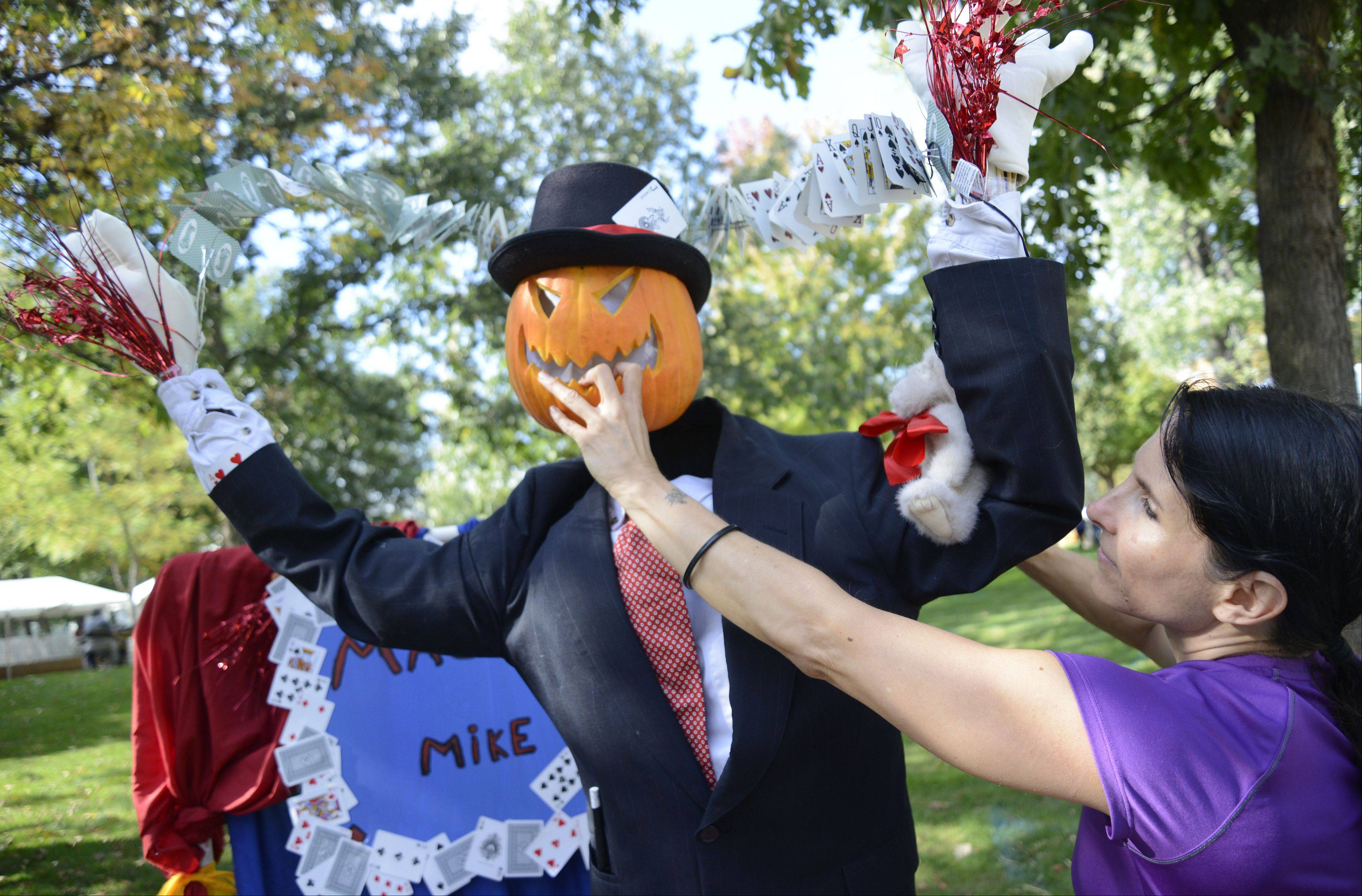 "Betty Marmolejo of Aurora readies head of ""Magic Mike"" her family's entry in the whimsical category in this weekend's Scarecrow Festival at Lincoln Park in St. Charles. This is the family's second time to enter the contest."