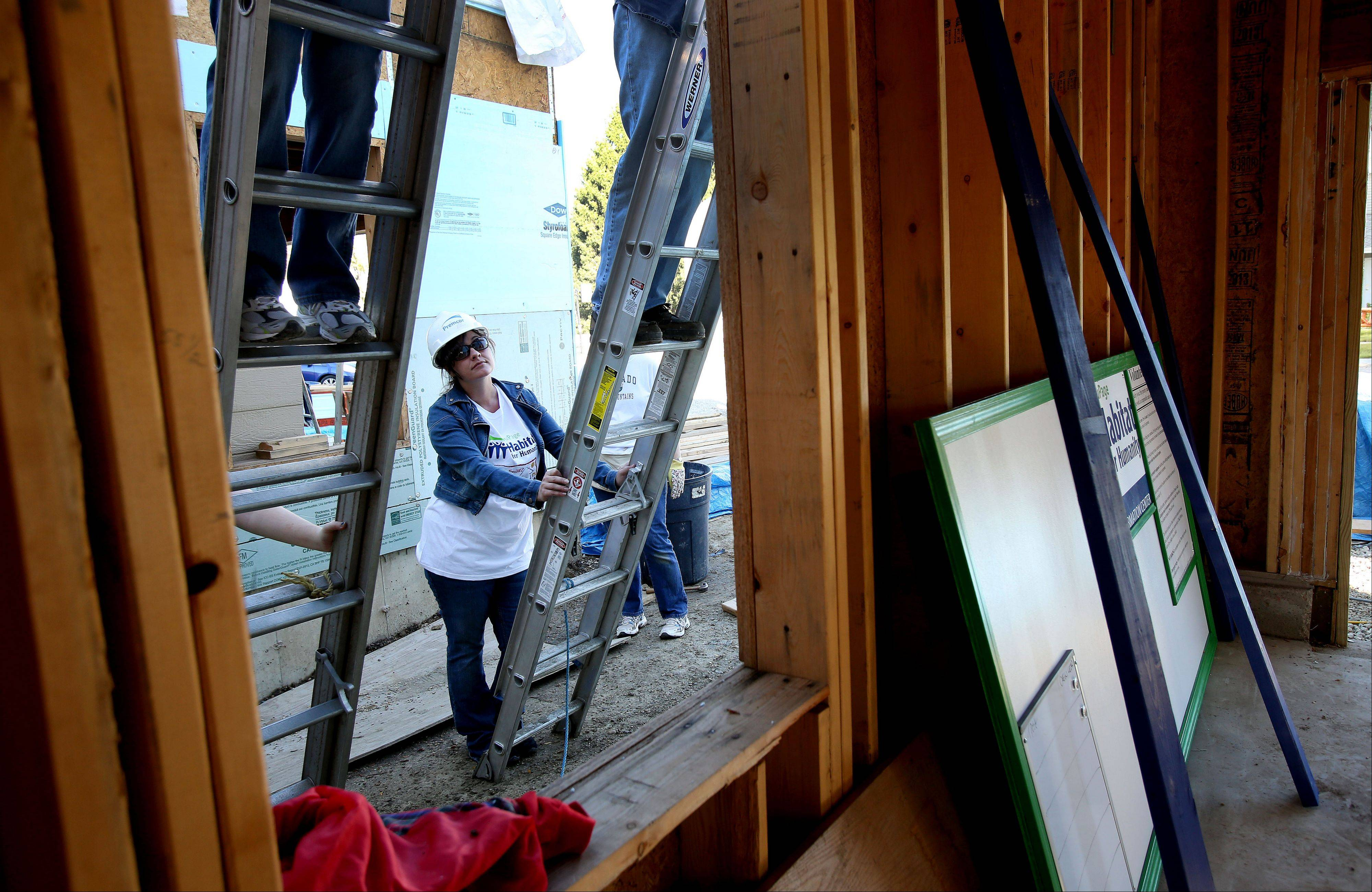 Tracy Bryson of Glen Ellyn holds a ladder as she works on a townhouse being built for her by Habitat for Humanity.