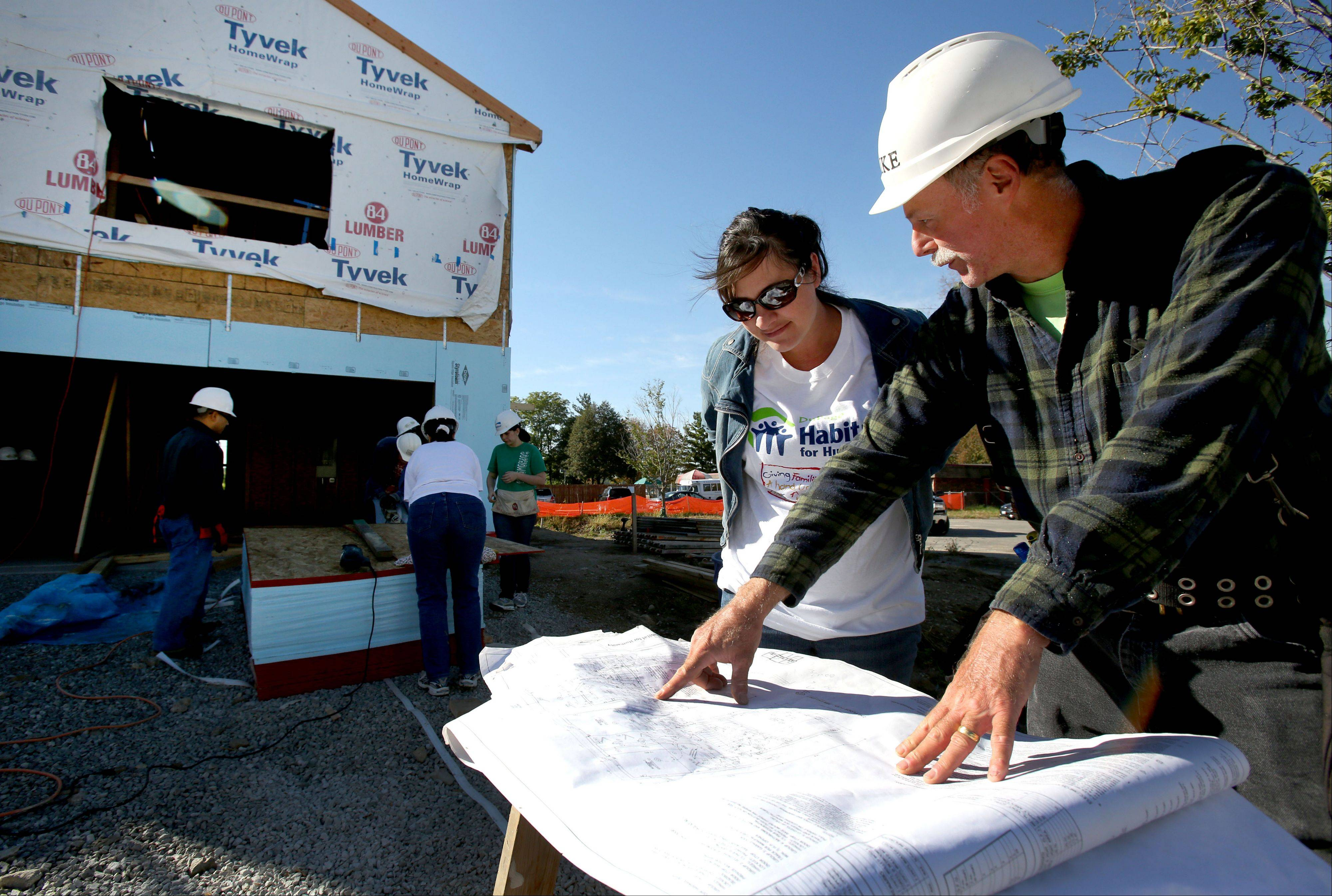 Volunteer crew manager Mike Hillenbrand shows Tracy Bryson of Glen Ellyn the blueprints of the townhouses Habitat for Humanity is building near Glen Ellyn.