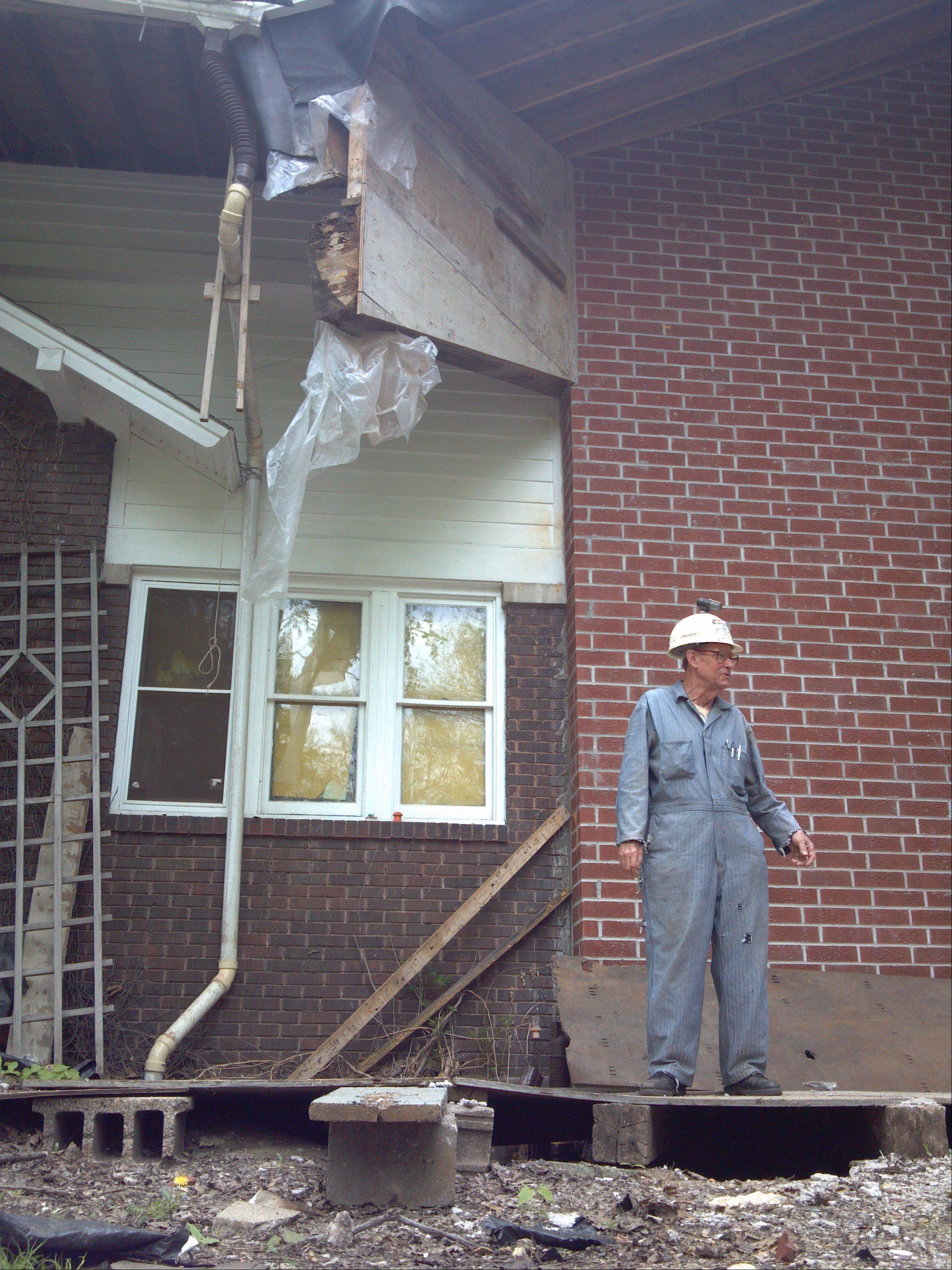 Clifford McIlvaine, who was sued by the city of St. Charles in an effort to get him to finish a project that he first pulled a permit for in 1975, stands on a landing between his original home to the left and new, super-insulated addition on the right, which he hopes to turn into a museum for his and his father's inventions, along with city memorabilia.
