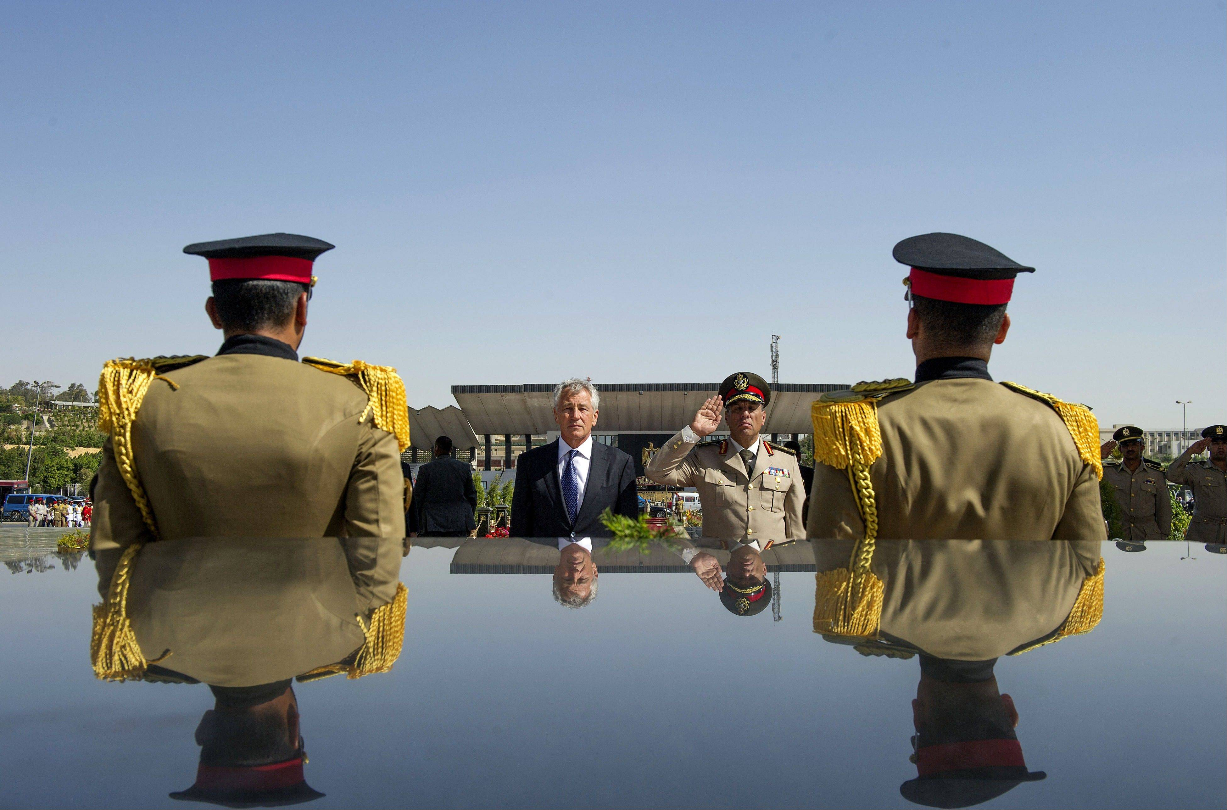 U.S. Secretary of Defense Chuck Hagel stands with an Egyptian army official before laying a wreath at the tomb of late President Anwar al-Sadat earlier this year. While dissatisfied with Egypt's progress toward reinstating a democratic government, the U.S. is holding out the possibility of restoring hundreds of millions of dollars in aid if its Mideast ally moves toward free and fair elections.