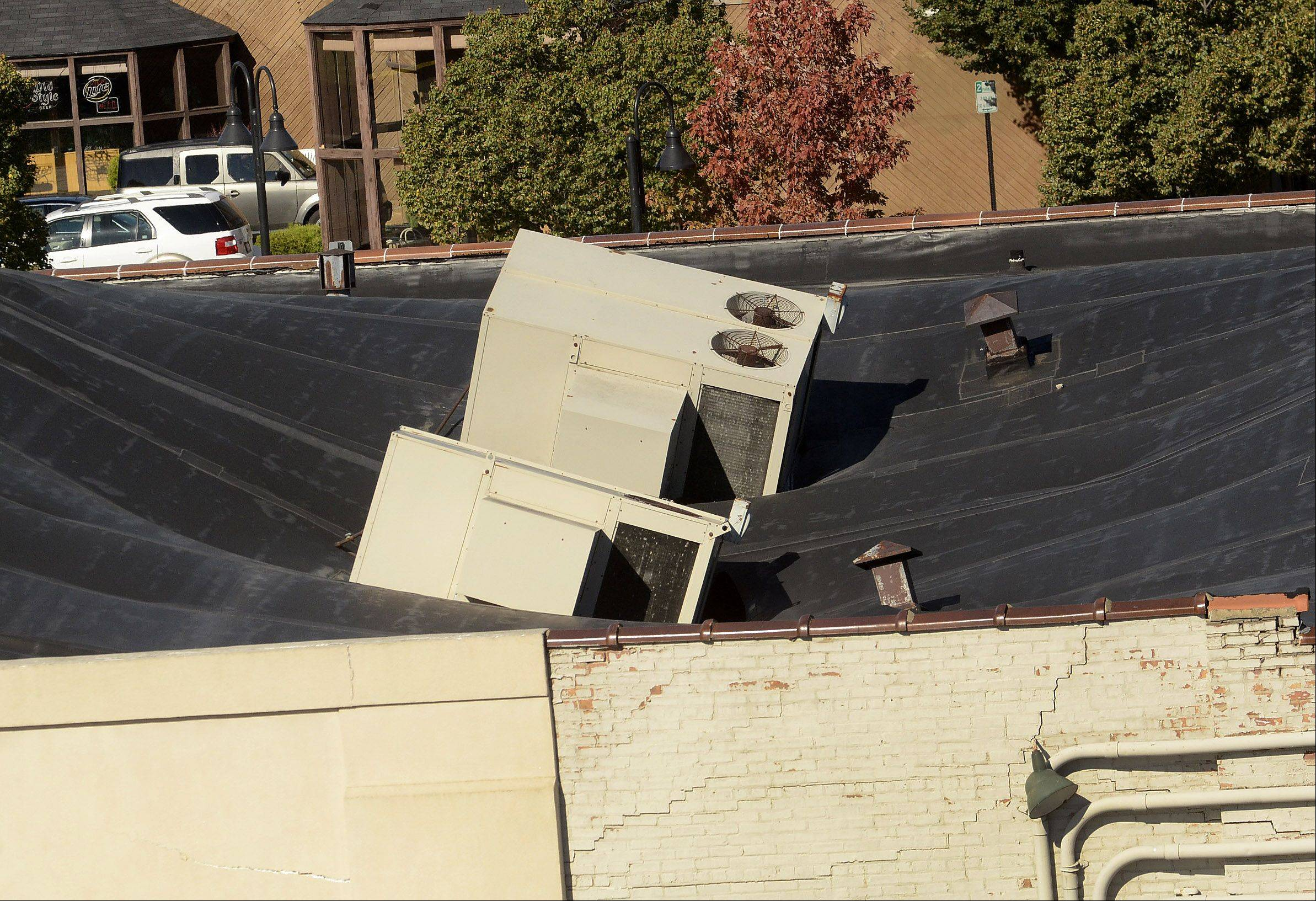 Two air-conditioning units sink into the roof of Tri-State Electronics in Mount Prospect. Crews will be watching today to see if the roof fully collapses.