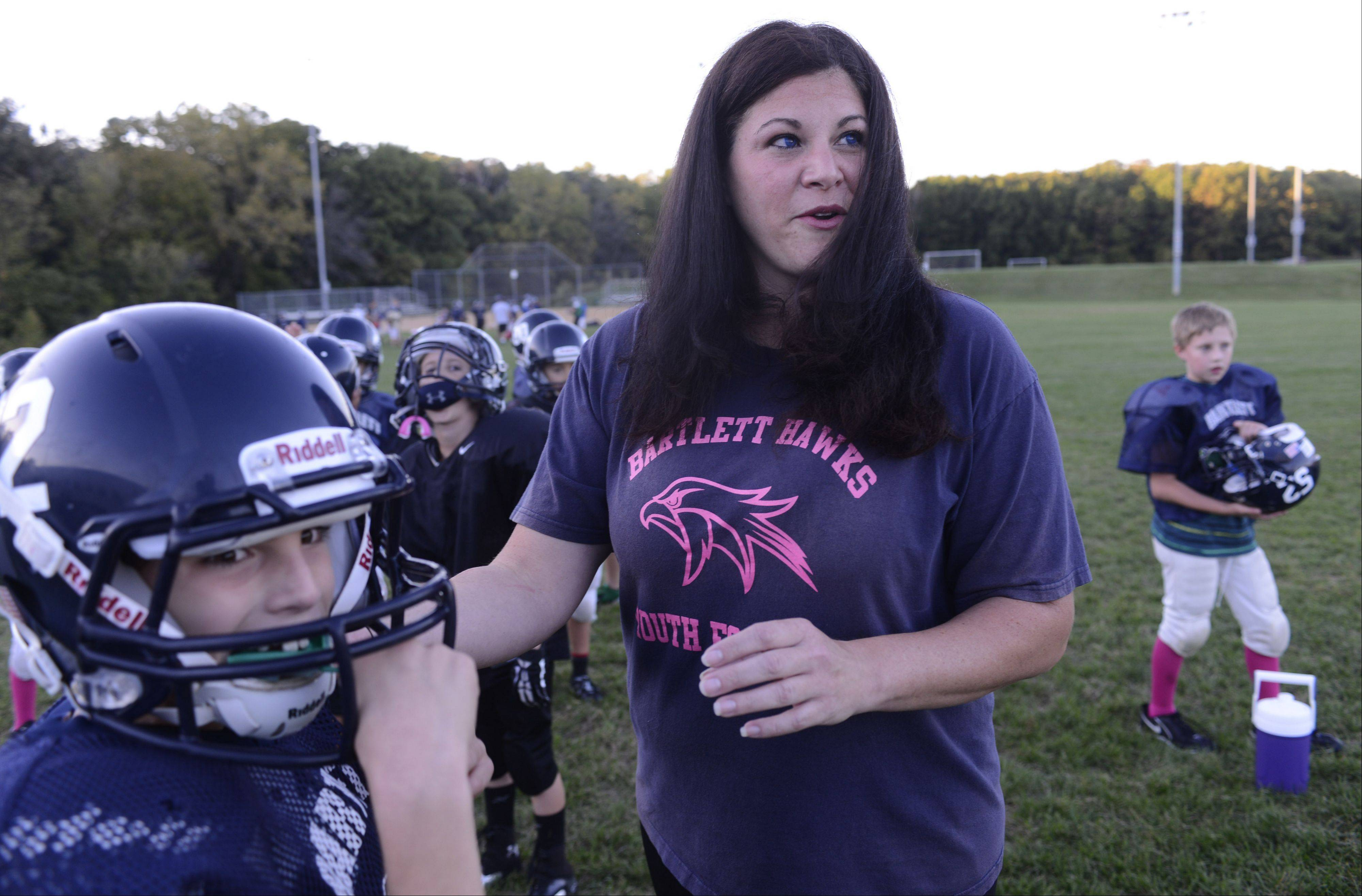 Jennifer Kmiecik of Bartlett helps her son Brandon, 9, snap on his helmet during a Bartlett Hawks youth football practice Wednesday. Kmiecik won $1,000 to go toward helmets and equipment after numerous Bartlett Hawks families nominated her for the Courtyard Marriott's Inspire Greatness Program.