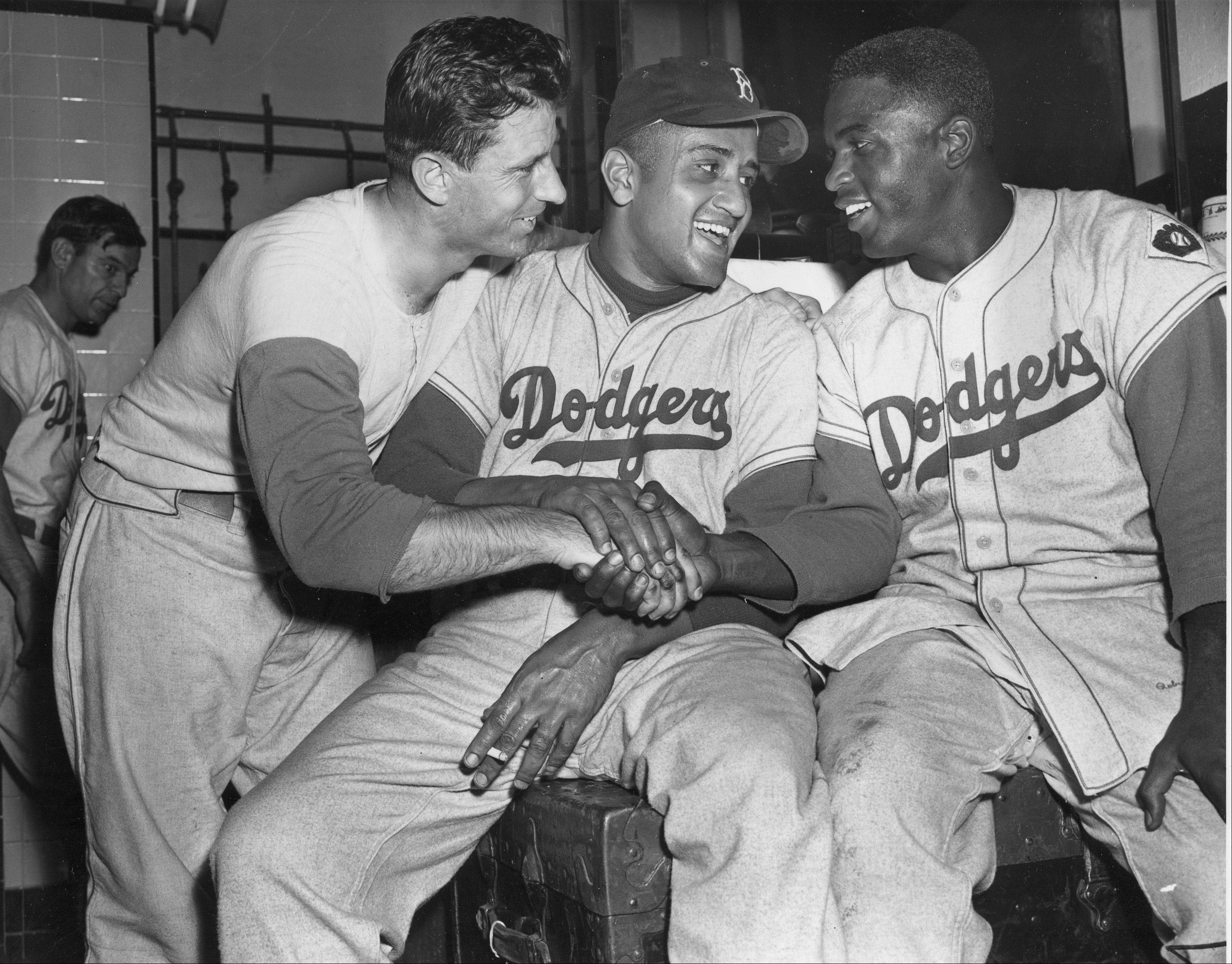Celebrating a clutch victory in 1951, Brooklyn Dodgers Andy Pafko, left, Don Newcomb, center, and Jackie Robinson shake hands in their dressing room.