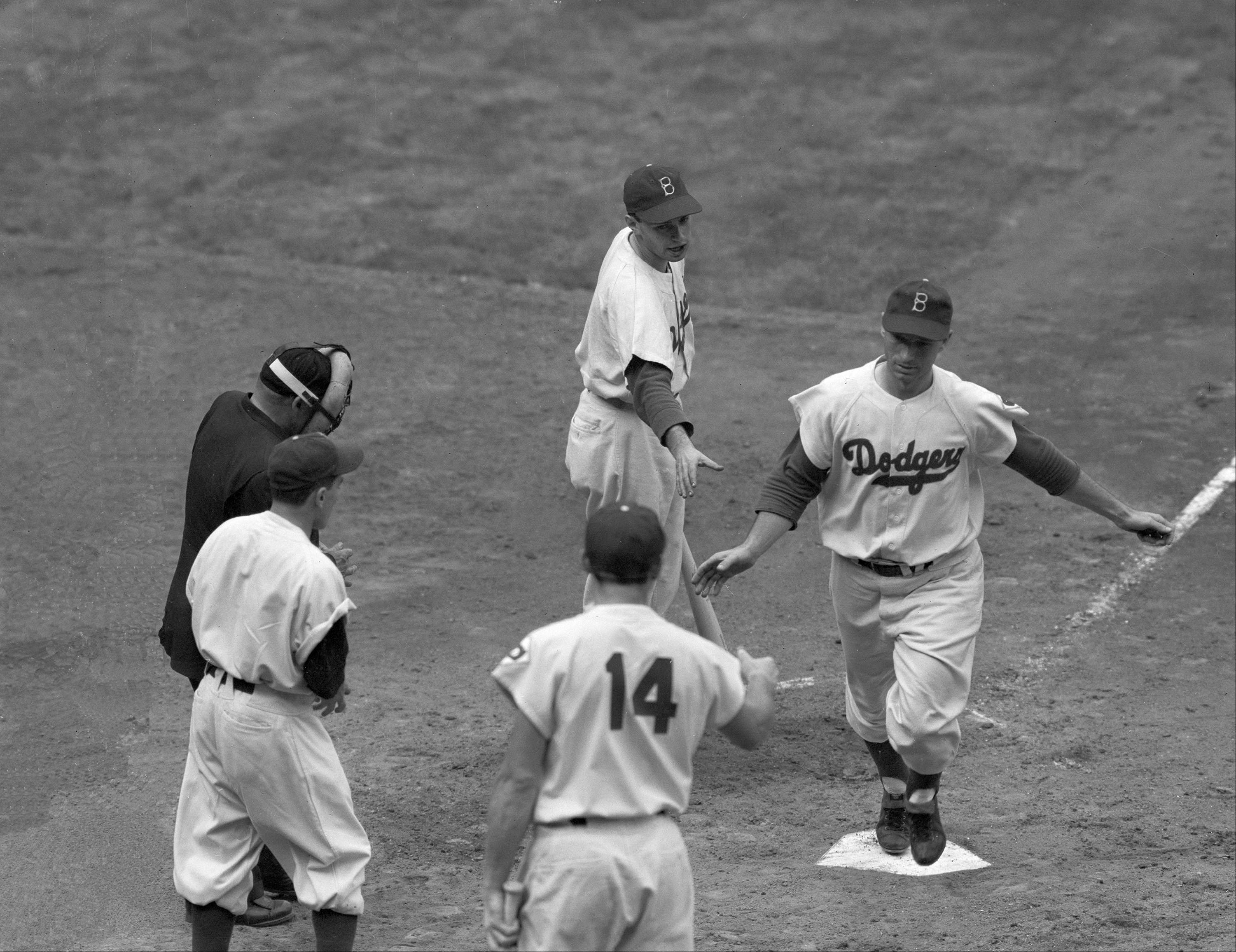 Scoring the first run in a memorable three-game series to decide the 1951 pennant, Brooklyn Dodger Andy Pafko touches the plate after hitting a homer. The series would end with Pafko watching a home run off the bat of Bobby Thomson to win the pennant for the New York Giants.