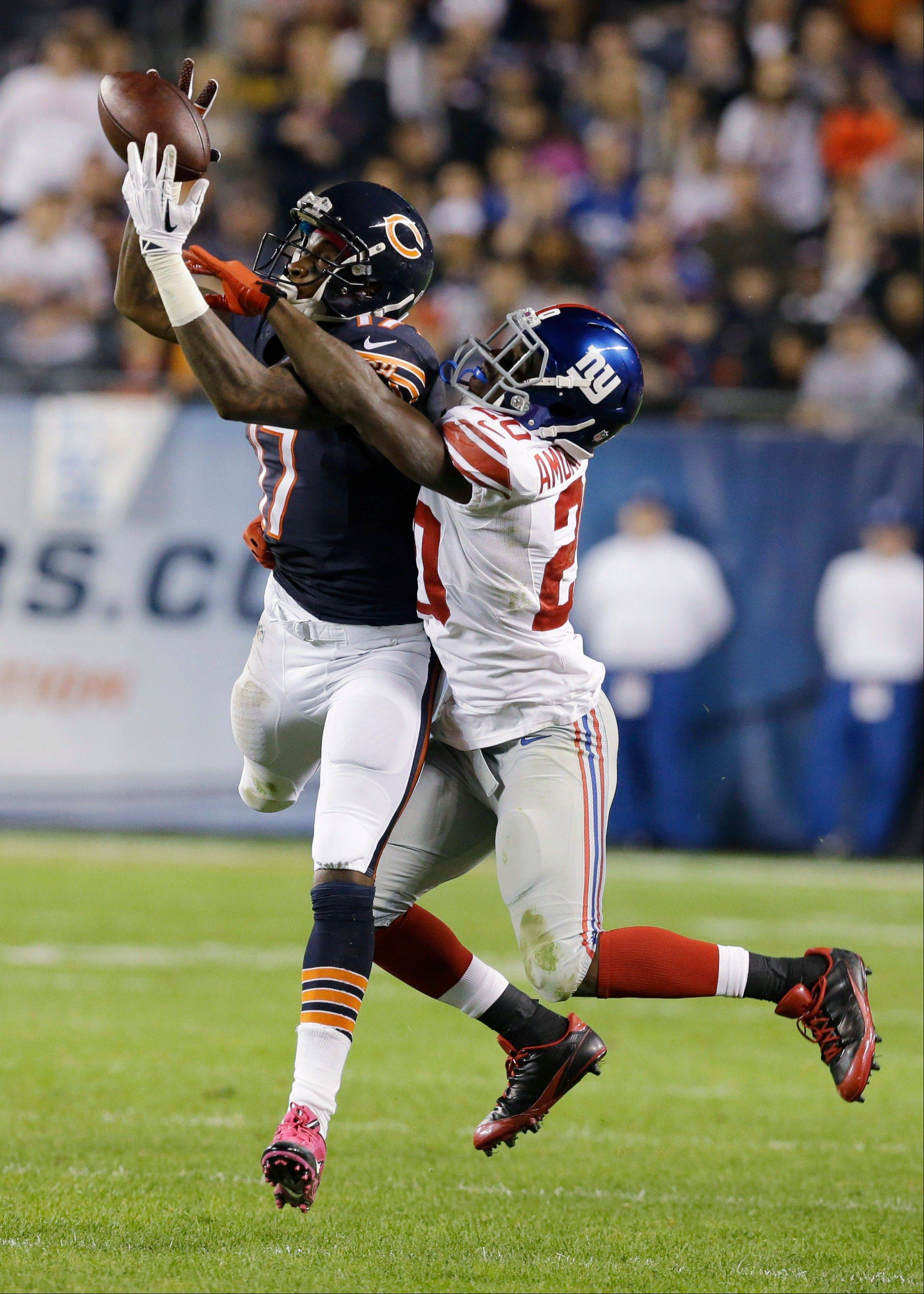 Chicago Bears wide receiver Alshon Jeffery (17) misses a catch under pressure from New York Giants cornerback Prince Amukamara (20) in the second half of an NFL football game, Thursday, Oct. 10, 2013, in Chicago.