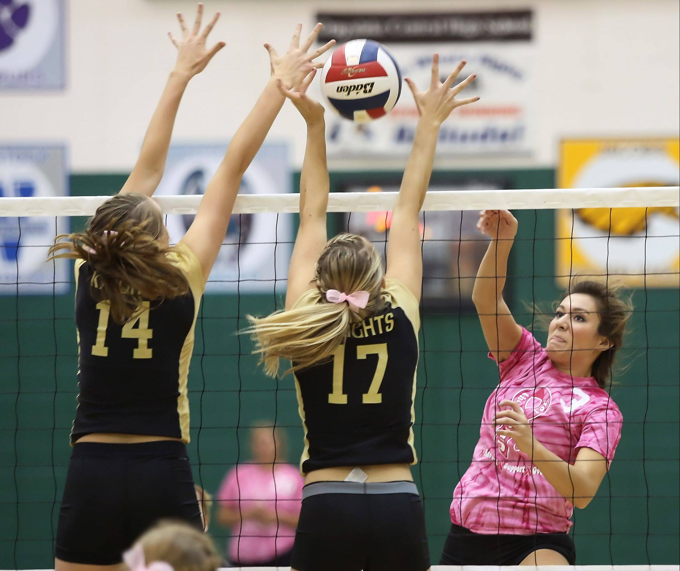 Grayslake Central hitter Gabi Casper slams the ball past Grayslake North blockers Kendall Buckman and Alaina Geissberger, left, during Thursday's match.