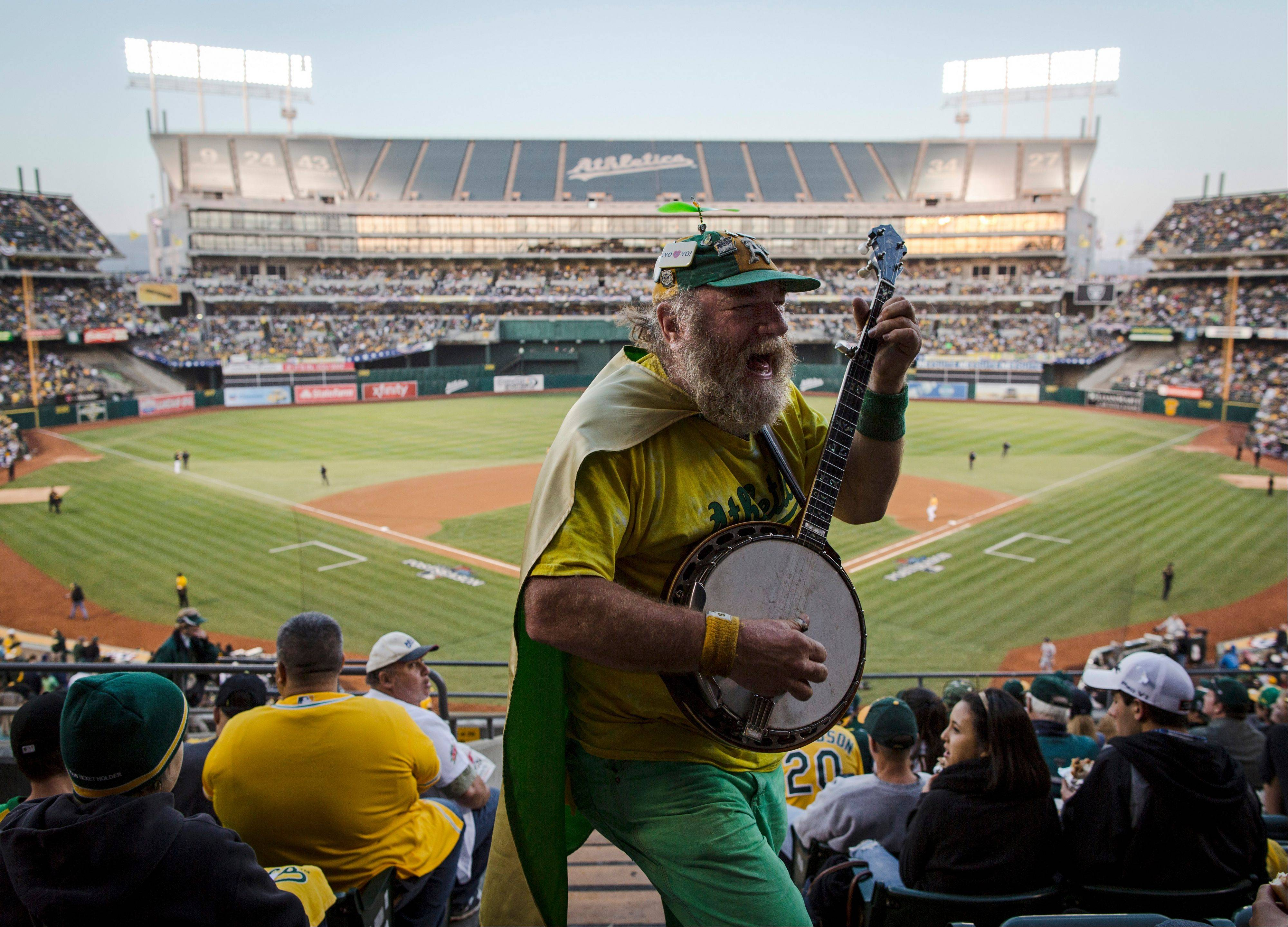 "Oakland fan ""Banjo Man"" (aka Stacy Samuels) plays for the crowd in the fifth inning of Game 5."