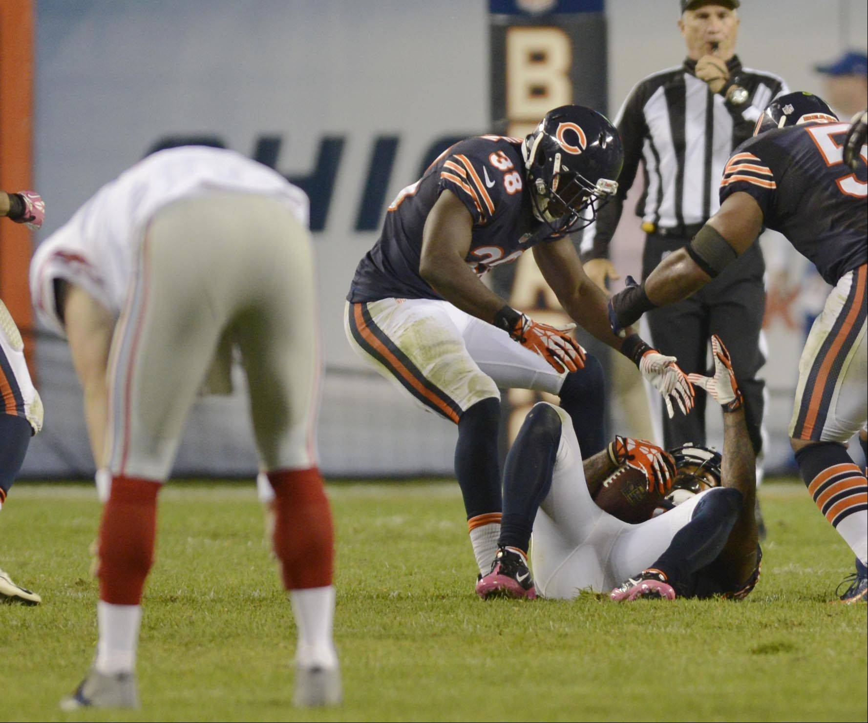 Chicago Bears cornerback Tim Jennings is helped up by teammates after his second interception of New York Giants quarterback Eli Manning, left, Thursday night at Soldier Field in Chicago.