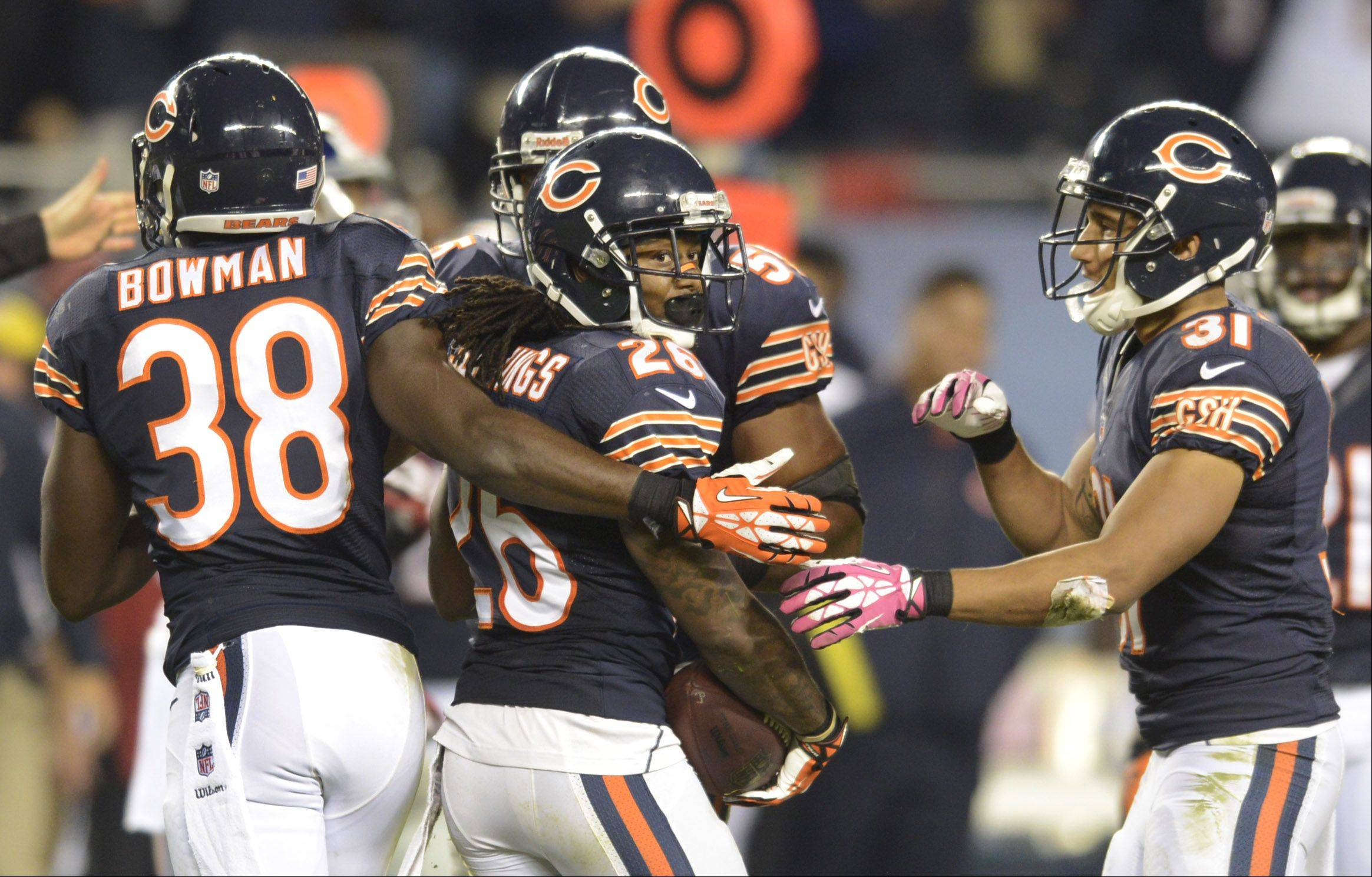 Chicago Bears cornerback Tim Jennings, middle, celebrates with his teammates including Zack Bowman, left, and Isaiah Frey after a key fourth-quarter interception.