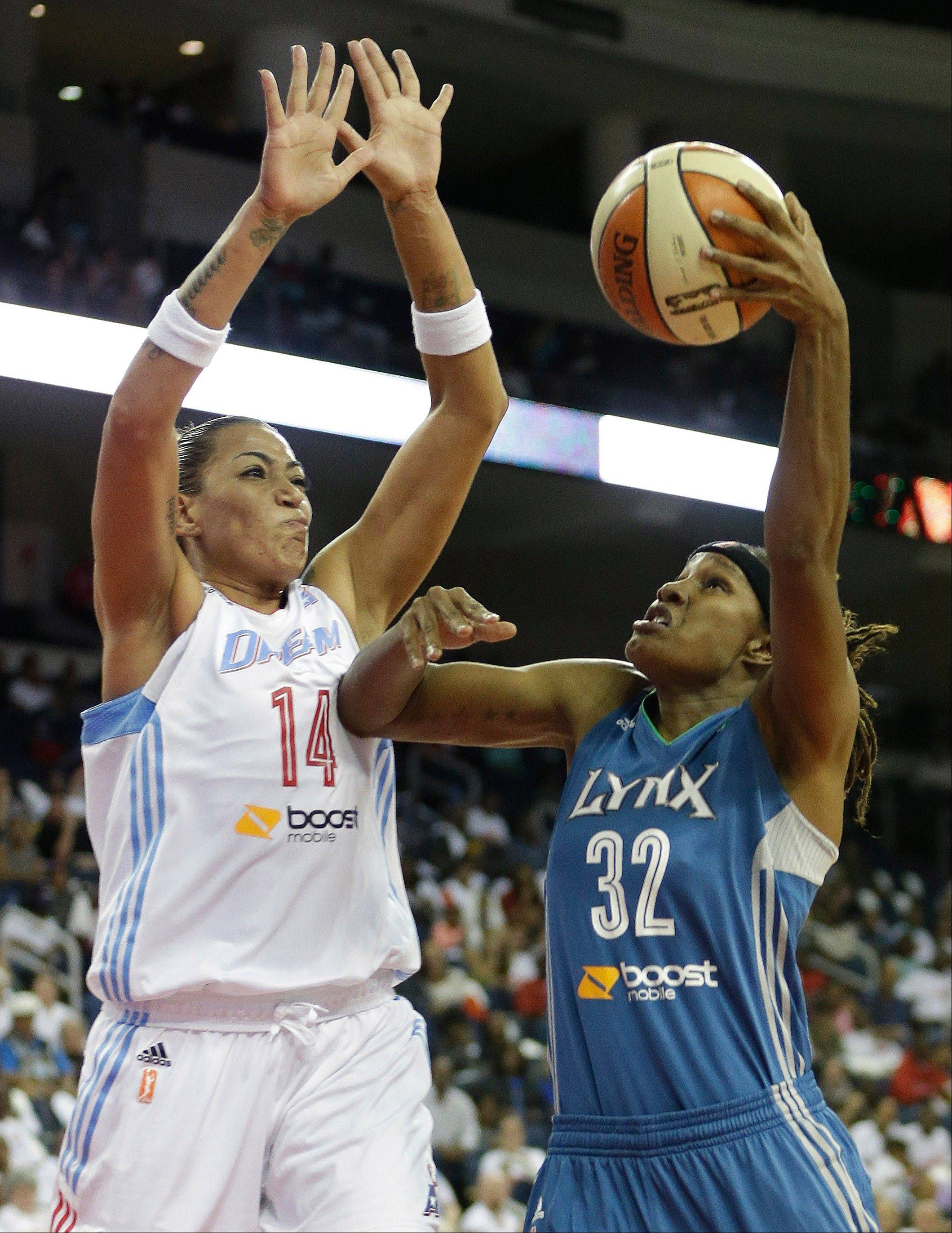 Minnesota's Rebekkah Brunson shoots as Atlanta's Erika de Souza defends during Game 3 of the WNBA Finals Thursday in Duluth, Ga.