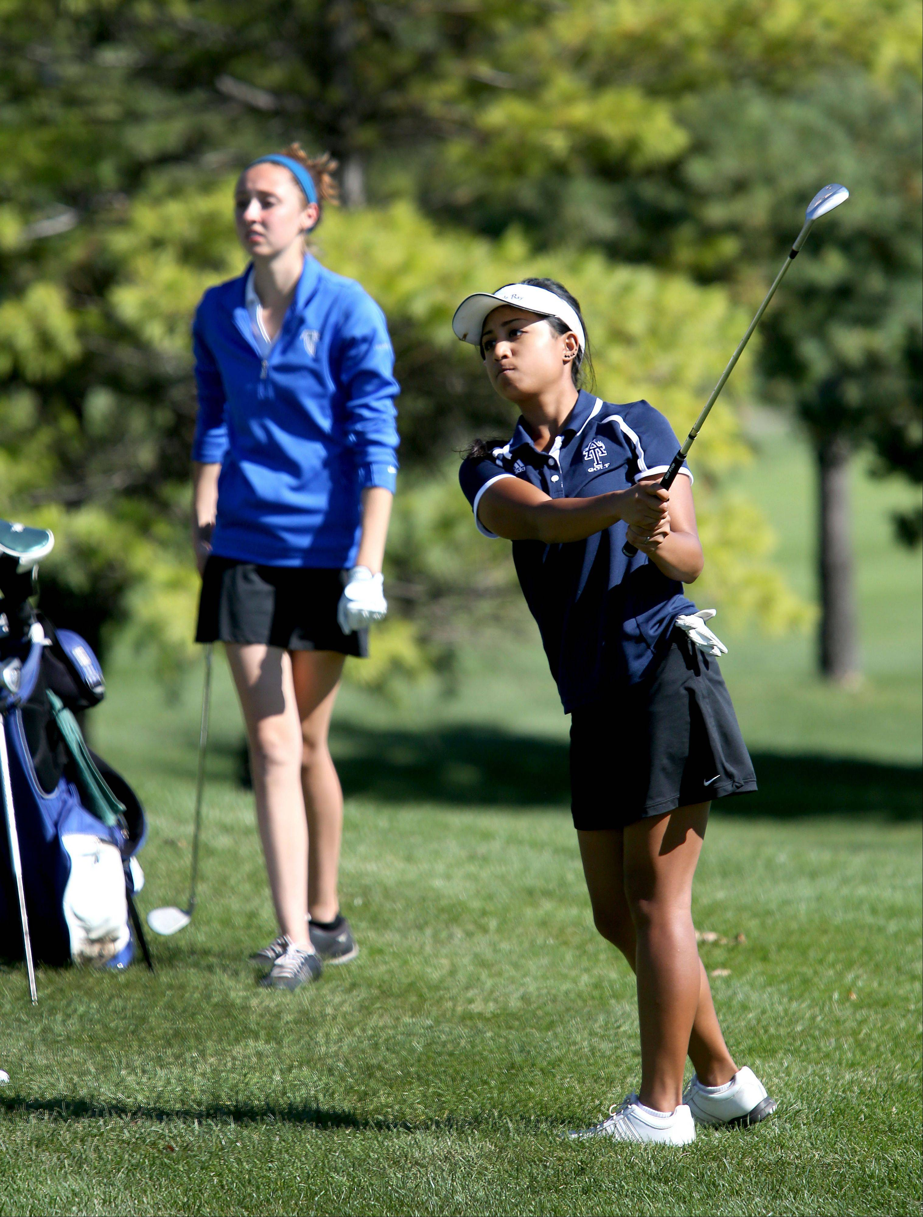 Gia De La Cruz of Addison Trail, right, watches her drive on the 11th tee as Caitlin Berry of Wheaton North looks on during Class AA Glenbard East regional girls golf at Glendale Lakes Golf Course in Glendale Heights on Wednesday.