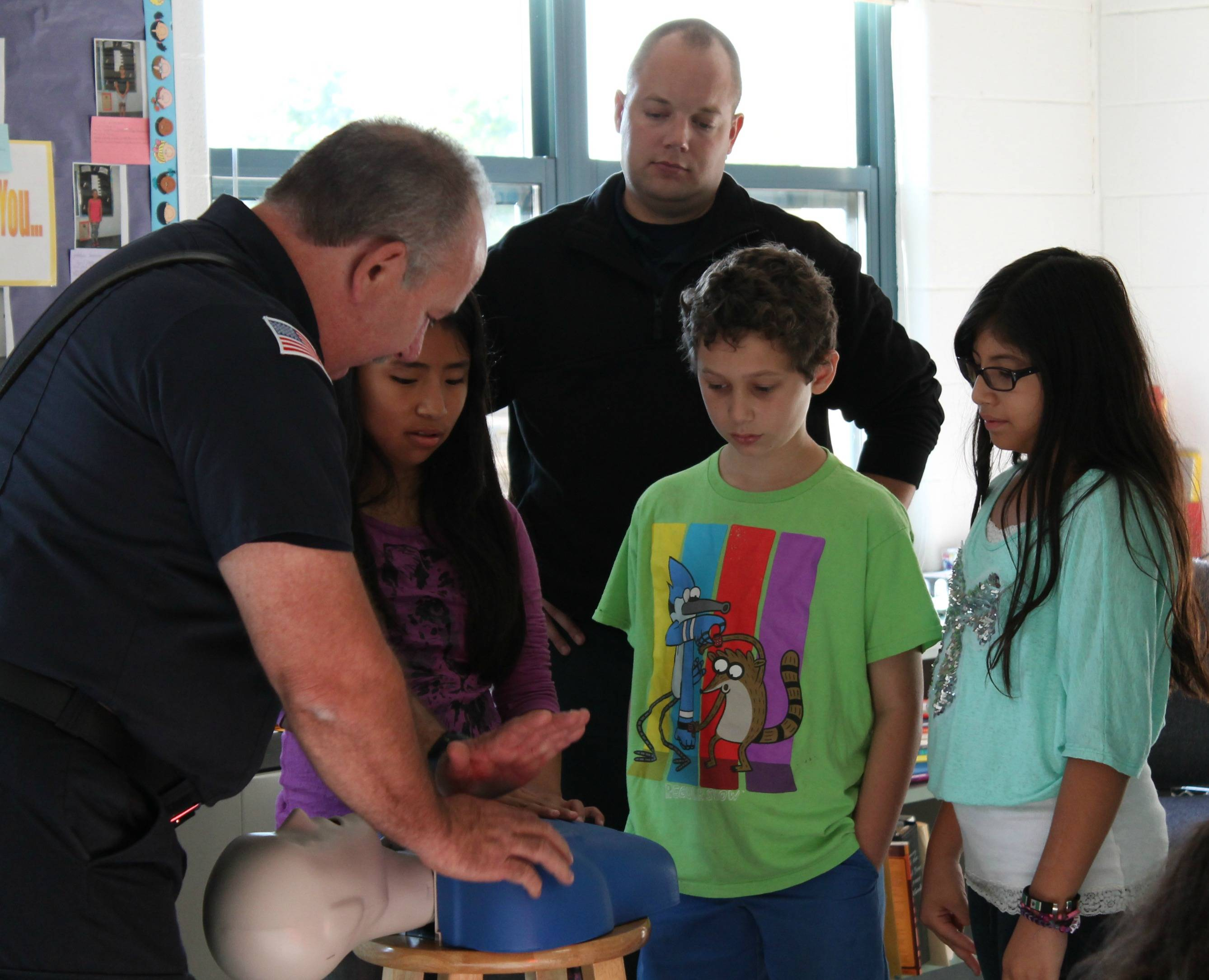 5th grade students at Currier Elementary School observe proper CPR technique demonstrated by fire fighter from West Chicago Fire Department.