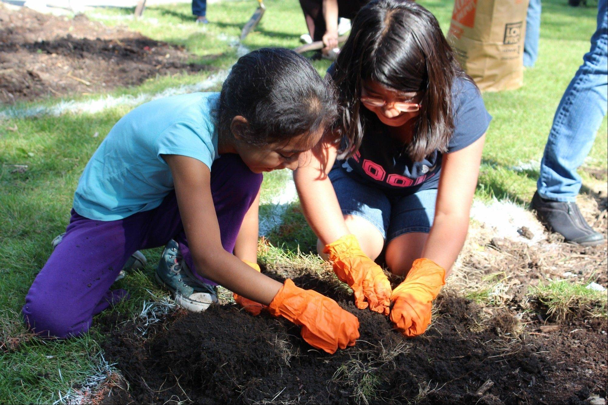 Third-graders Sheila M. (left) and Sharlyn C. dig up grass to expand the heart-shaped flower bed in front of Kilmer Elementary School on Friday, Sept. 27.