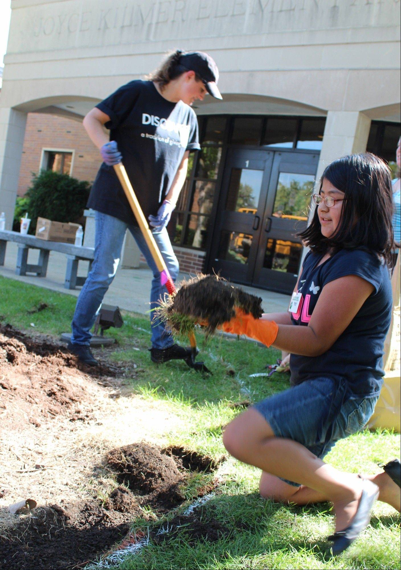 A volunteer from Discover Financial Services works to expand the heart-shaped flower bed in front of Kilmer Elementary School as third-grader Sharlyn C. removes excess sod.