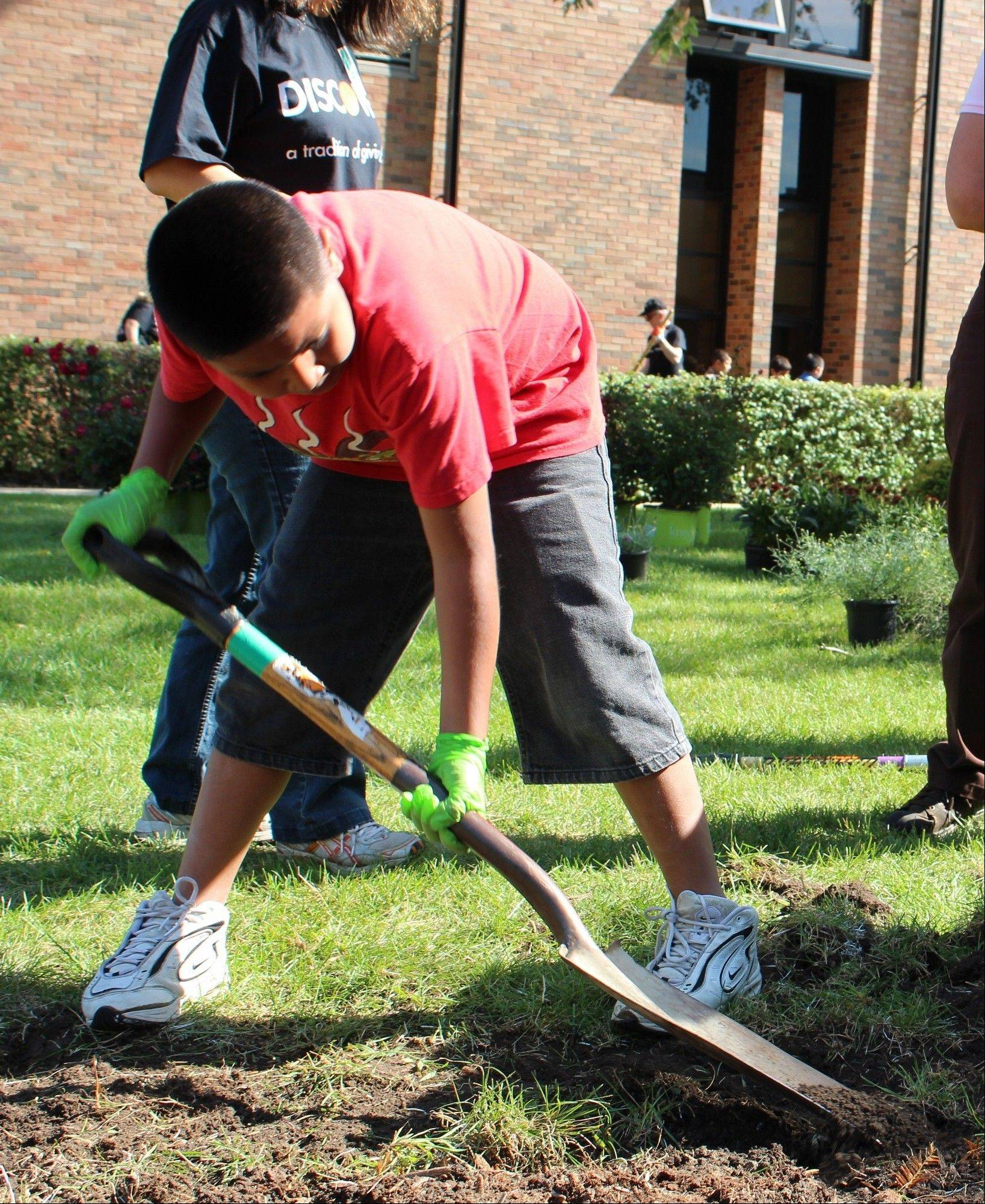 Christian O., a fifth-grader at Kilmer Elementary School, works to make space for a butterfly garden in front of the school on Friday, Sept. 27.