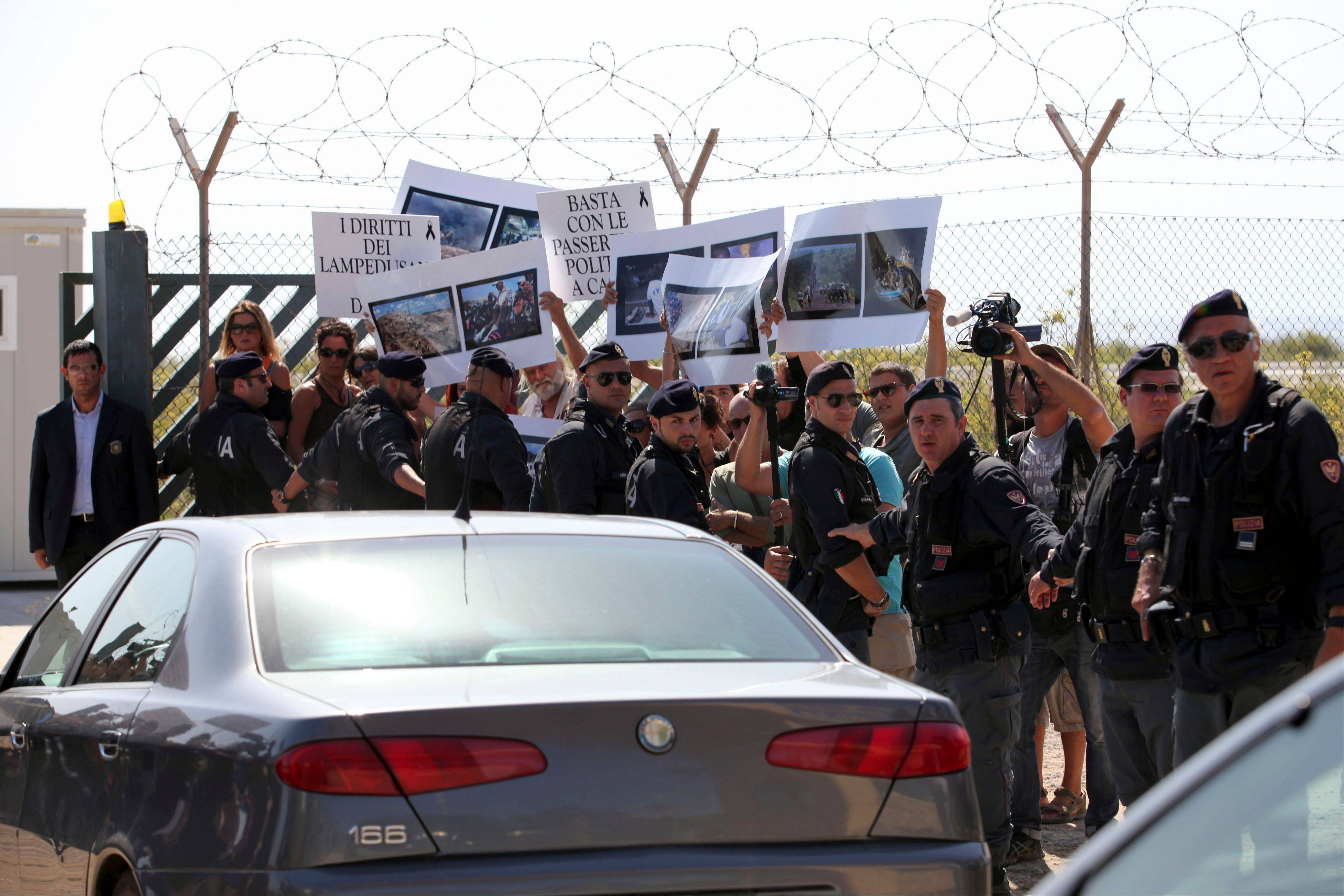 Protesters, held back by Italian riot policemen, show placards Wednesday reading:�Lampedusa�s rights adrift� as a motorcade escorting EU Commission President Jose Manuel Barroso and Italian Premier Enrico Letta leaves Lampedusa�s airport, Italy. Barroso visited Lampedusa with Premier Enrico Letta, who announced that the victims of the disaster would receive a state funeral.