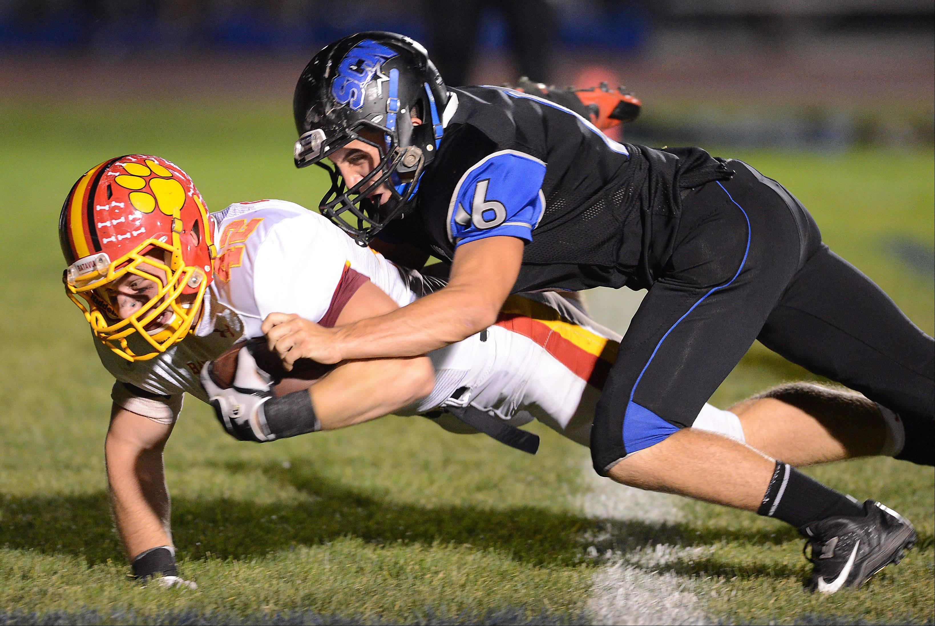 Batavia�s Kevin Green dives across the goalline under pressure from St Charles North�s Tyler Bell for a touchdown to put the Bulldogs up 19-0 .