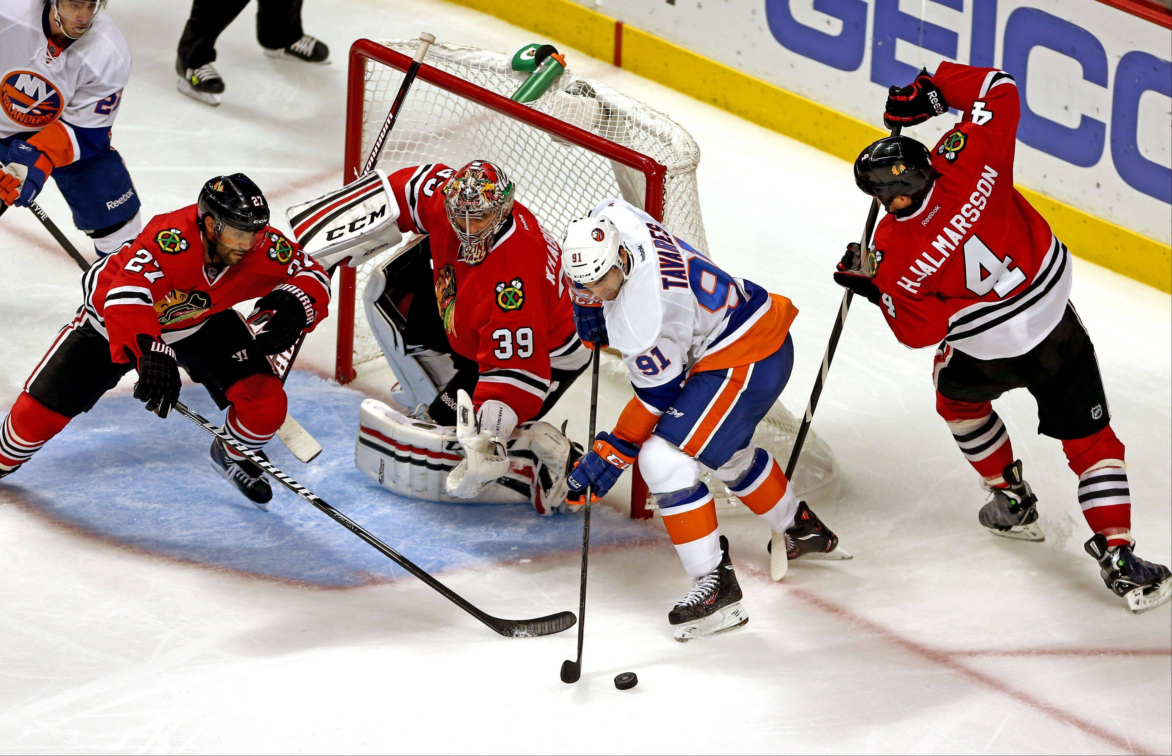 John Tavares of the Islanders draws a crowd near the Hawks net late in the third period, including goalie Nikolai Khabibulin and defensemen Johnny Oduya and Niklas Hjalmarsson at the United Center on Friday night.
