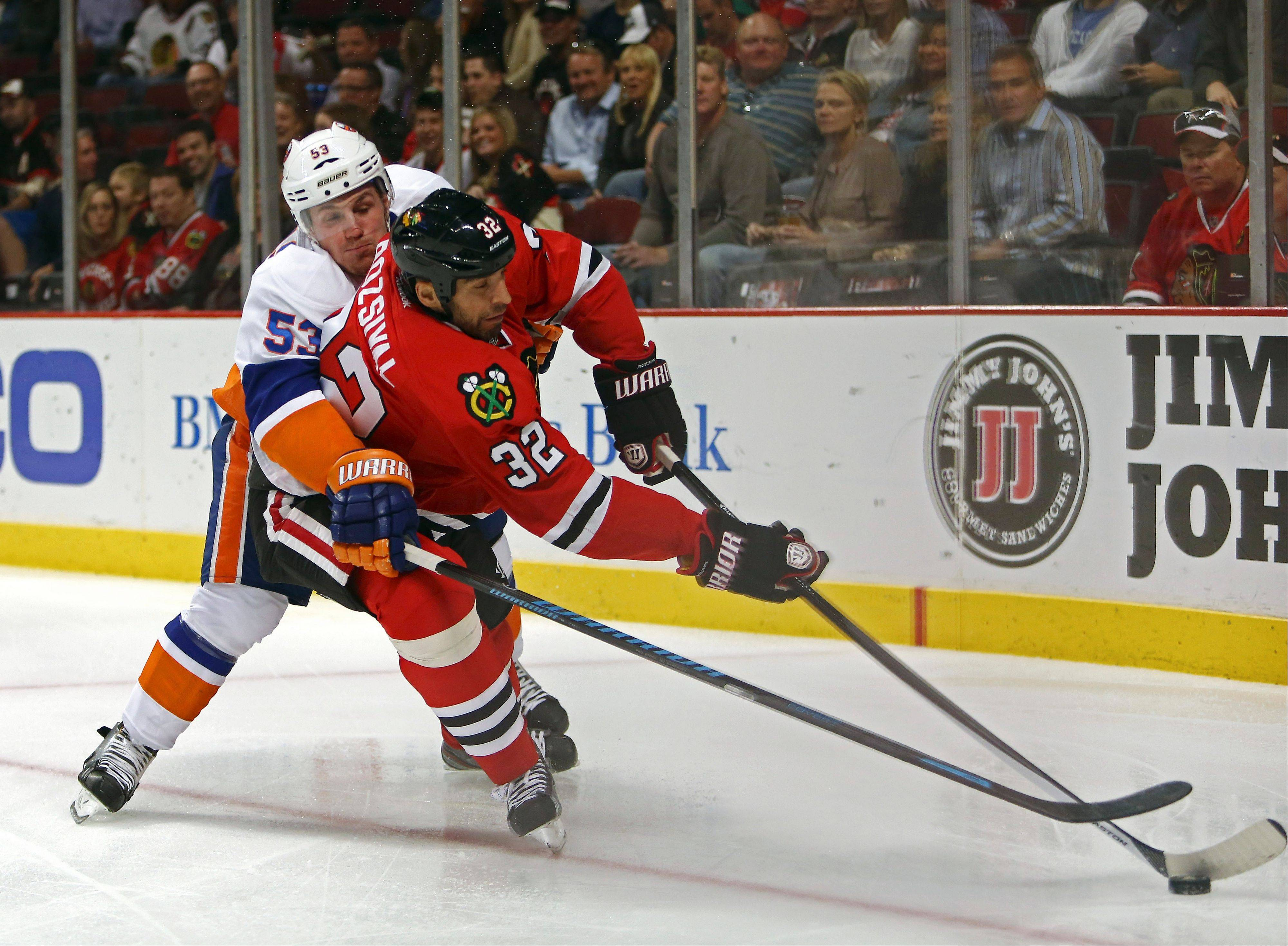 New York Islanders' Casey Cizikas tries to poke the puck away from Chicago Blackhawks' Michal Rosival during the first period of an NHL hockey game in Chicago on Friday, Oct. 11, 2013. (AP Photo/Charles Cherney)