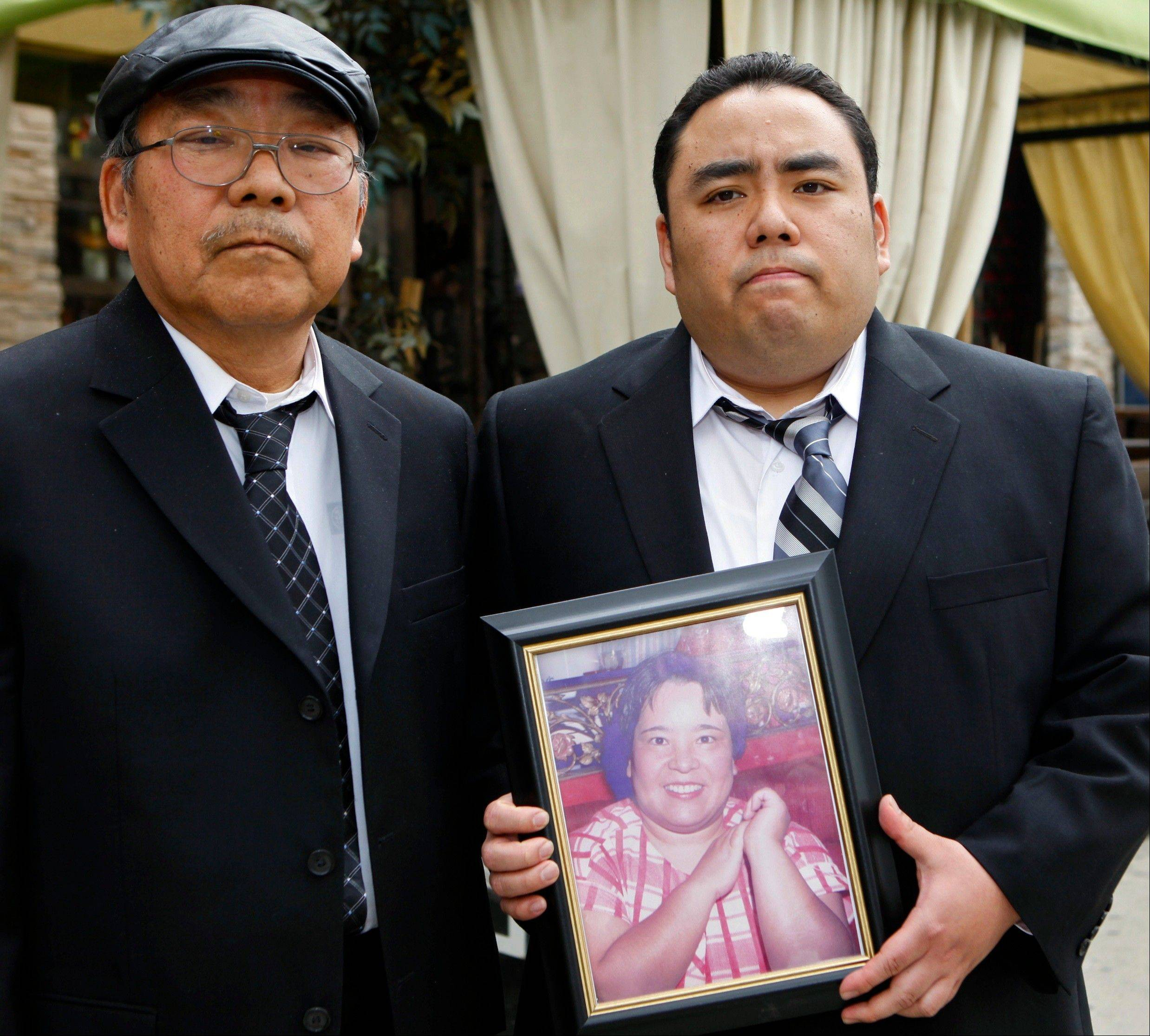 "Jeffrey Uno, right, and his father, Peter Uno, the son and husband of Noriko Uno, in framed photo, who died in an alleged ""sudden unintended acceleration"" crash in a Toyota Camry in August 2009, in Los Angeles."