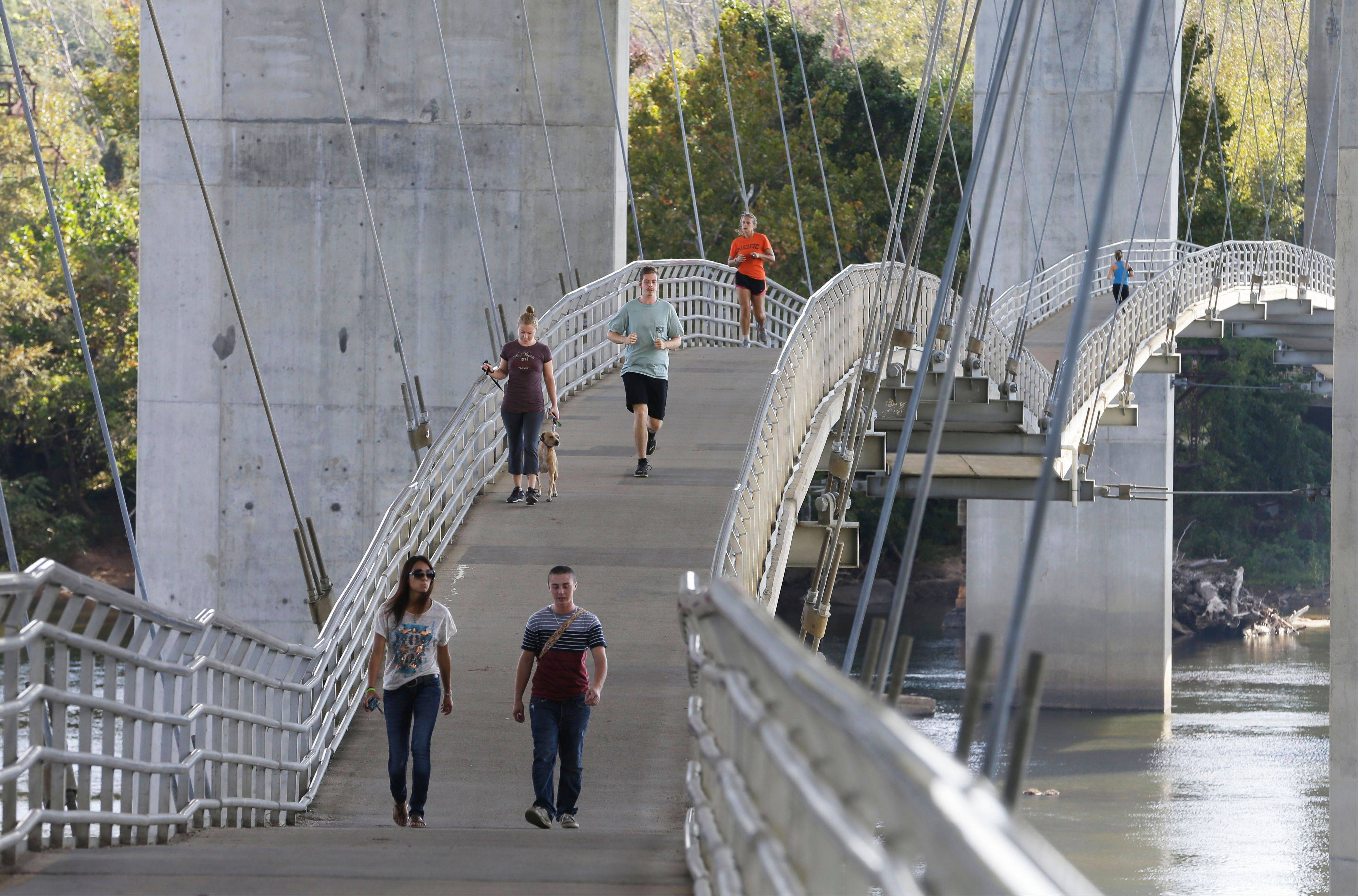 Runners and pedestrians traverse a bridge suspended under the Lee Bridge over the James River from Belle Isle in Richmond, Va.