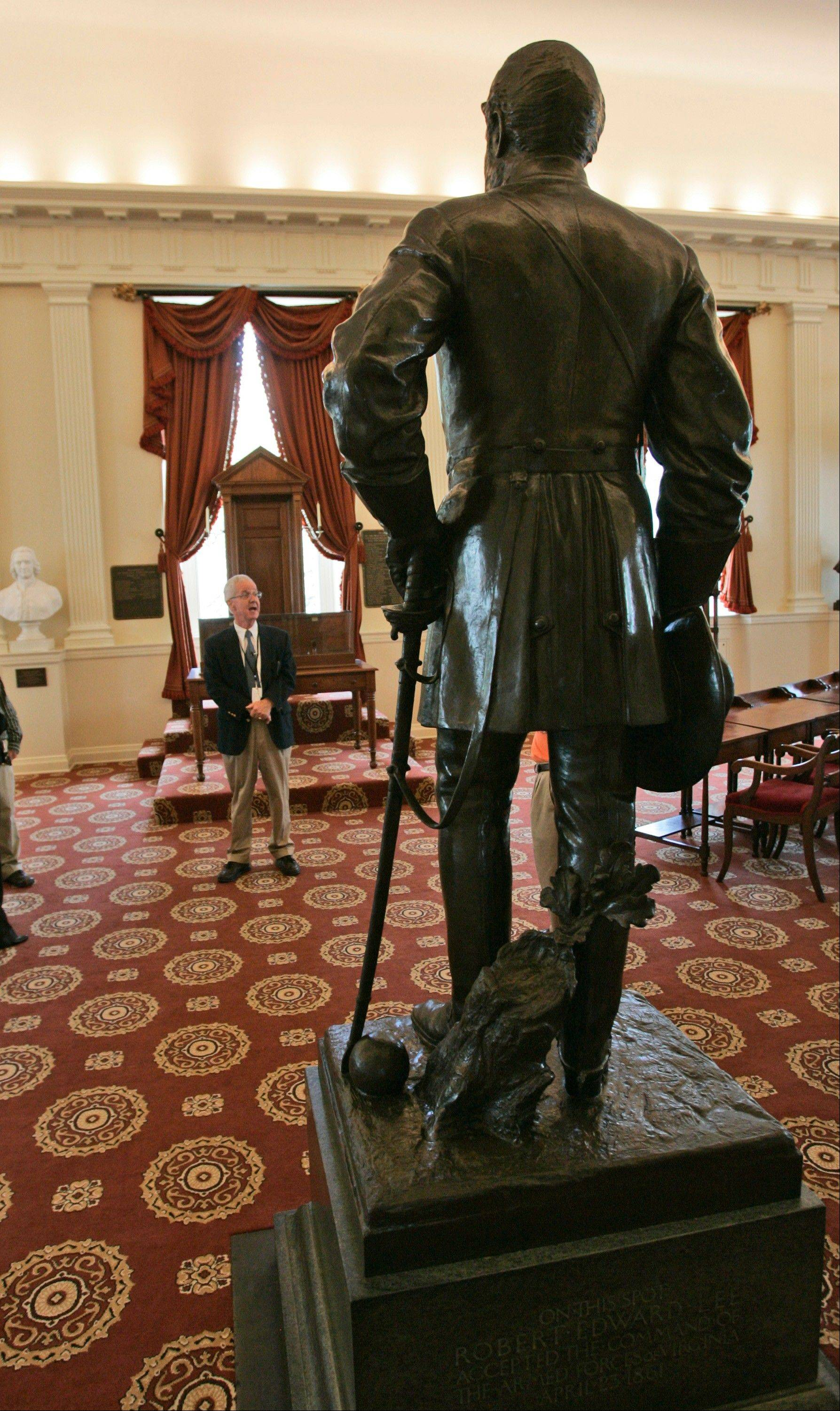 A tour guide leads a tour in the Old Senate Chambers at the State Capitol in Richmond, Va. Statues of Virginia historic figures dot the grounds.
