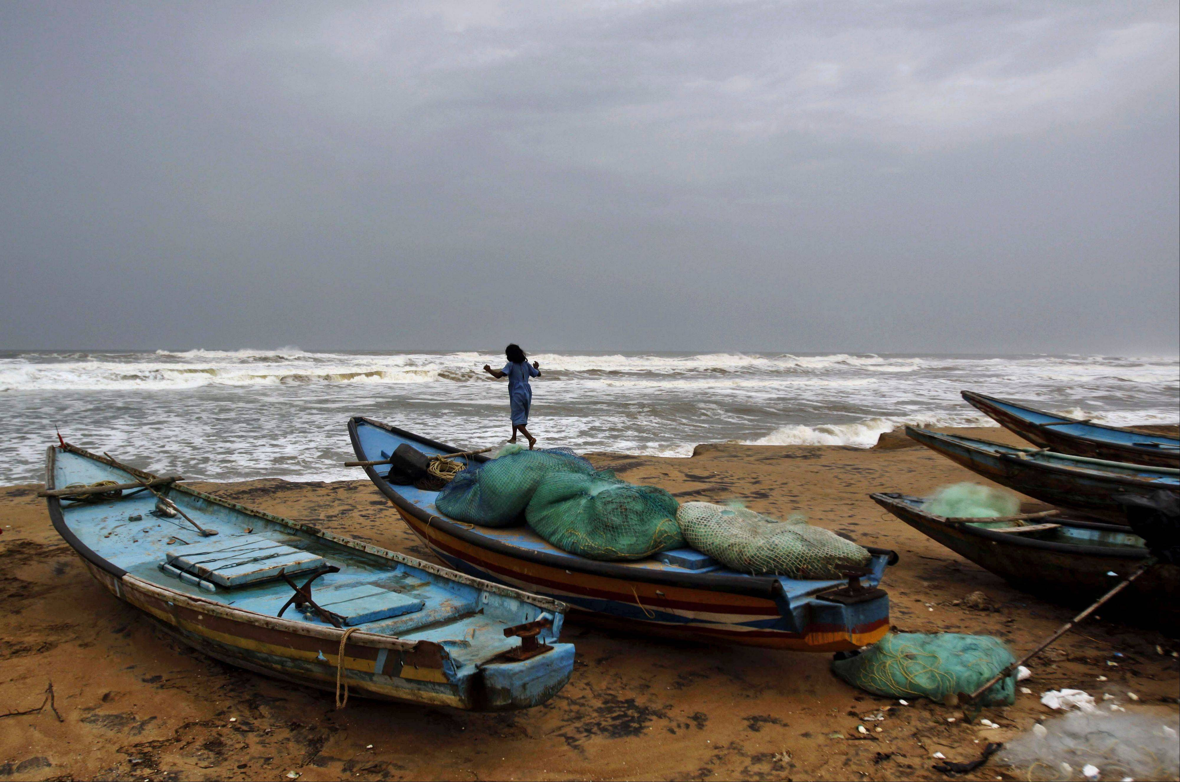"A young Indian girl plays Friday on top of an anchored boat at the Bay of Bengal coast in Gokhurkuda in Ganjam district. The Indian Meteorological Department warned that a massive cyclone Phailin was a ""very severe cyclonic storm."""