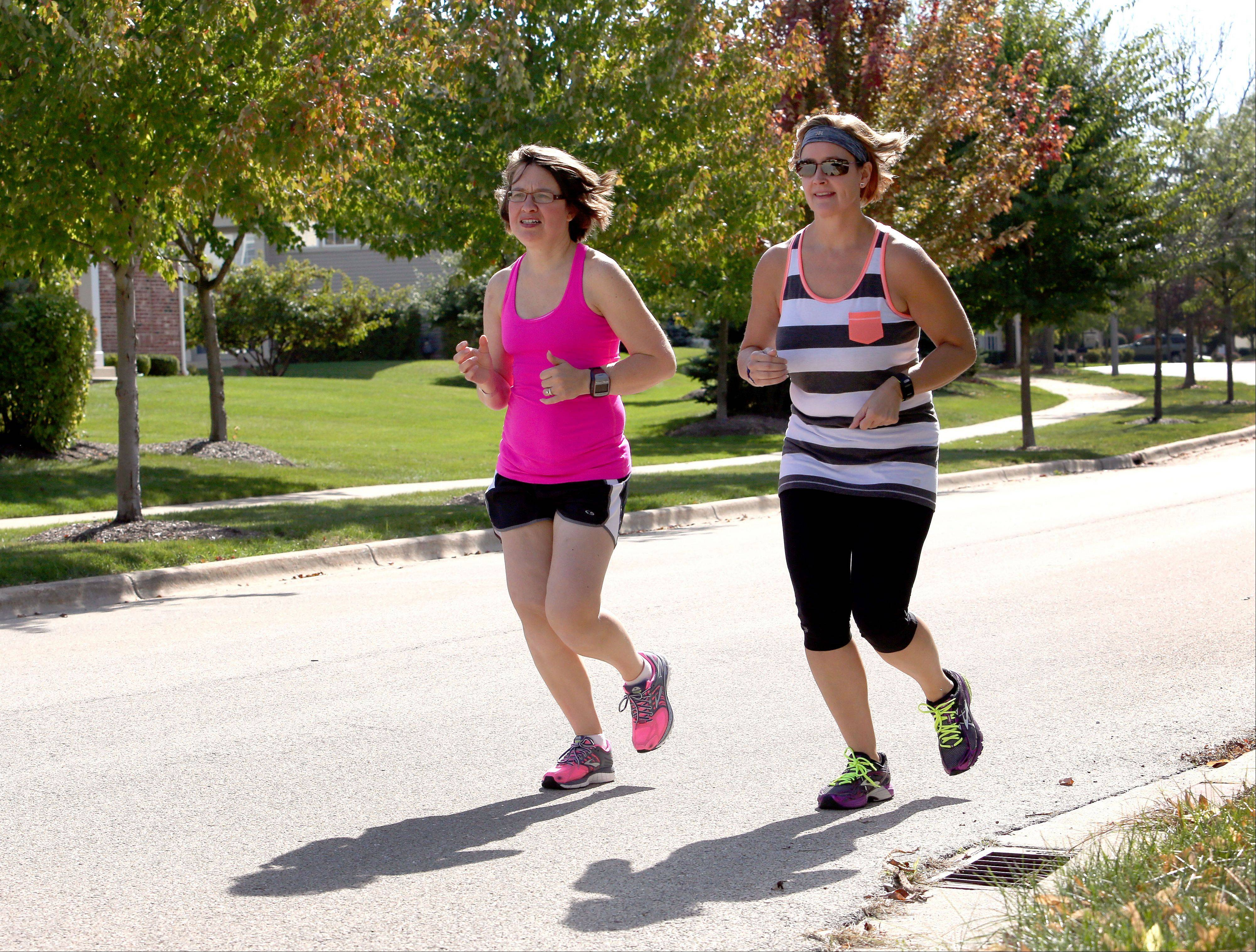 Marathon runners Danielle Steimel, left and Carrie Gasik, both of Aurora, take a short run as they train for the Chicago Marathon on Sunday.