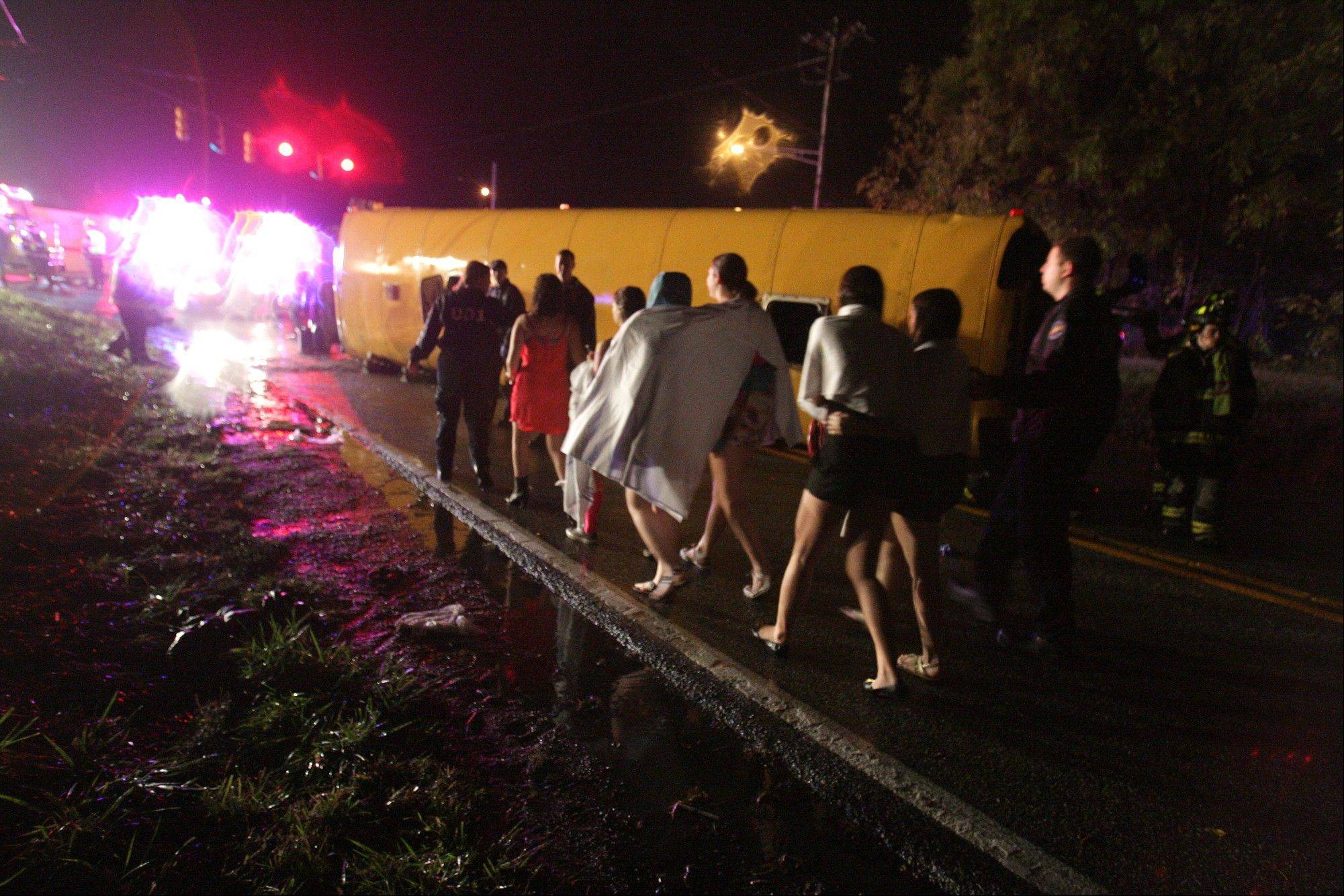 Passengers walk past a bus that overturned after colliding with a car carrier truck.