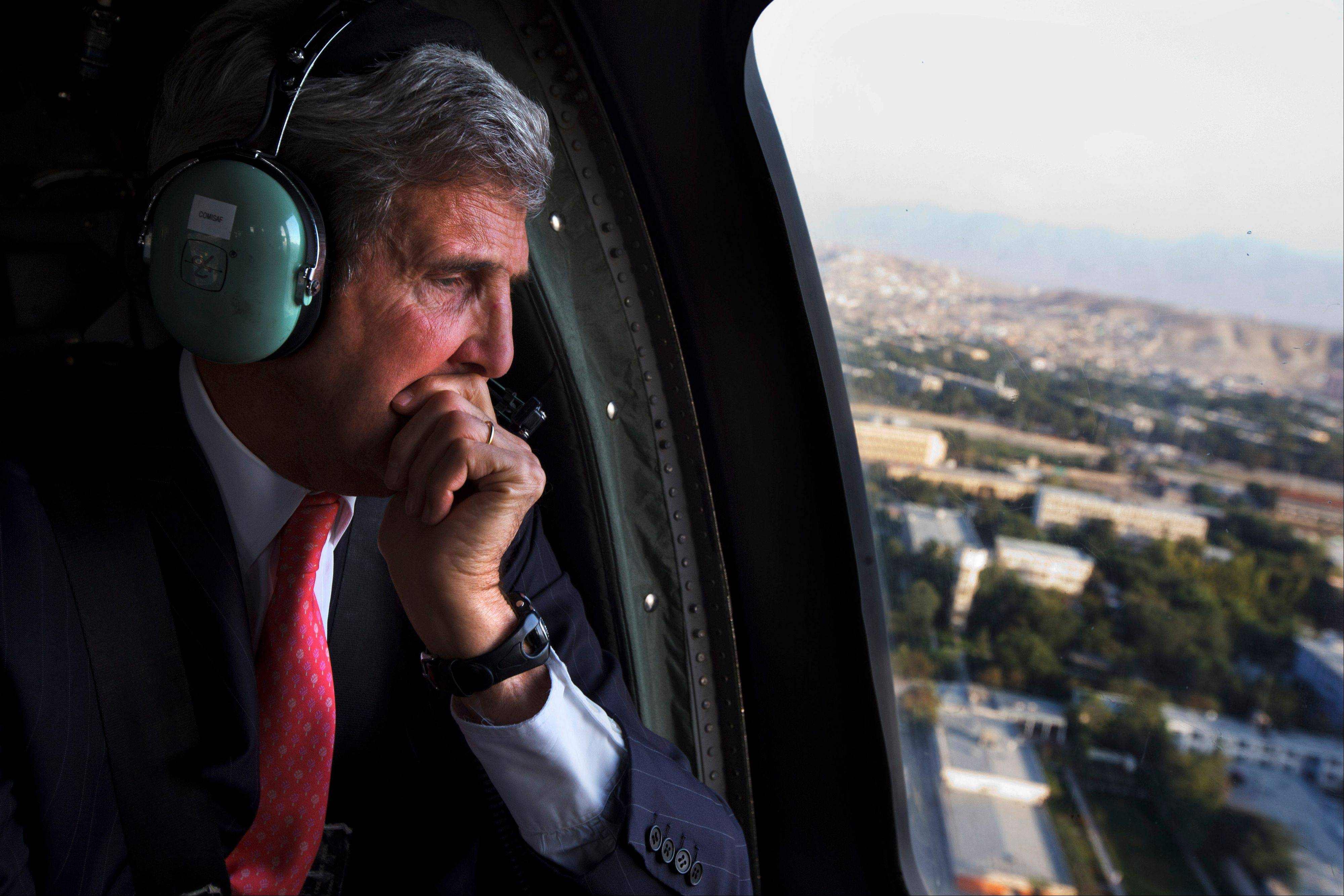 U.S. Secretary of State John Kerry looks out the window en route to the ISAF headquarters after arriving on an unannounced visit in Kabul, Afghanistan, Friday, Oct. 11, 2013. Kerry flew to Afghanistan Friday for urgent talks with Afghan President Hamid Karzai as an end of October deadline looms for completing a security deal that would allow American troops to remain in Afghanistan after the end of the NATO-led military mission next year.