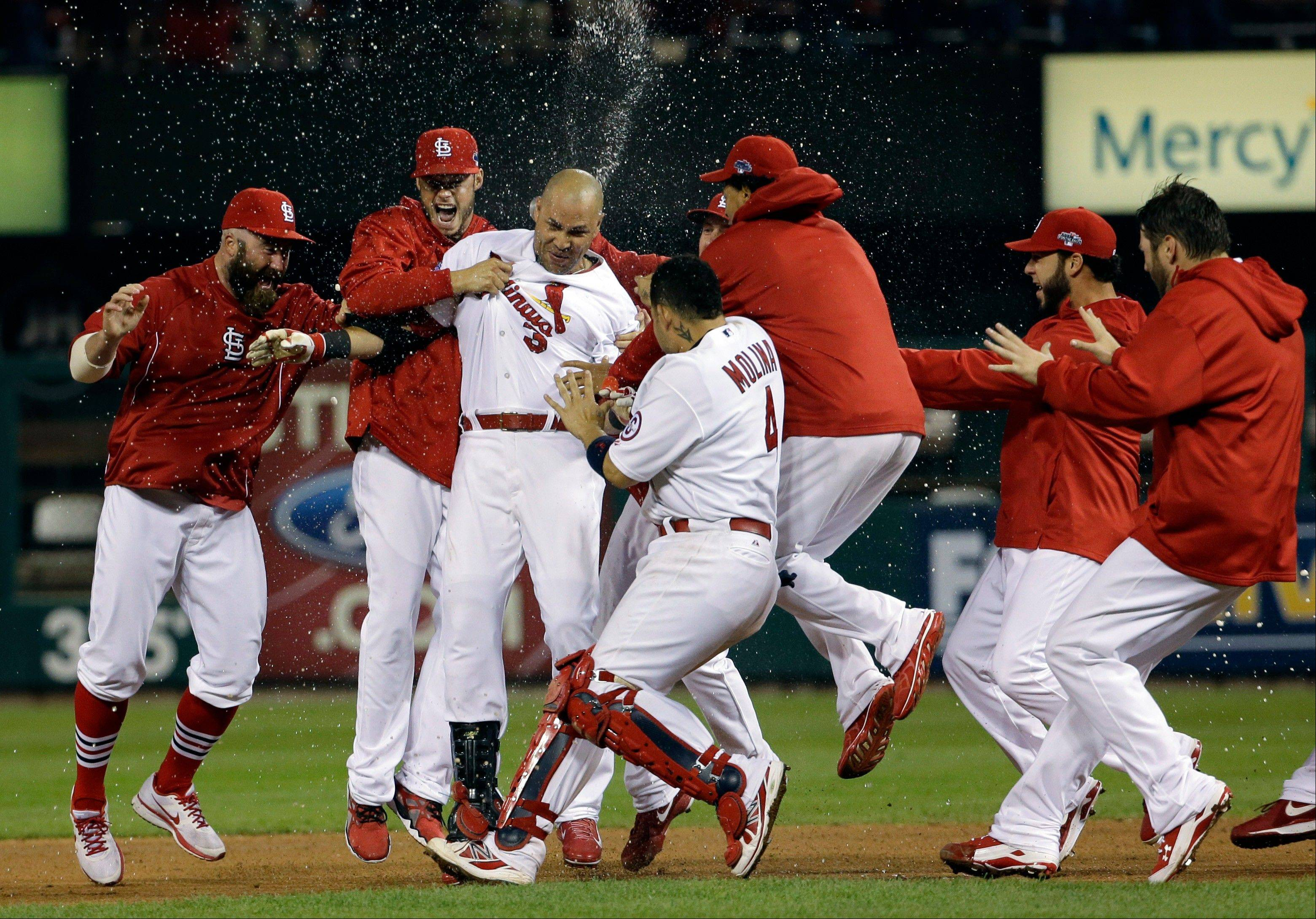 The Cardinals mob Carlos Beltran after his game-winning hit during the 13th inning of Game 1 against the Los Angeles Dodgers early Saturday morning in the National League Championship Series.