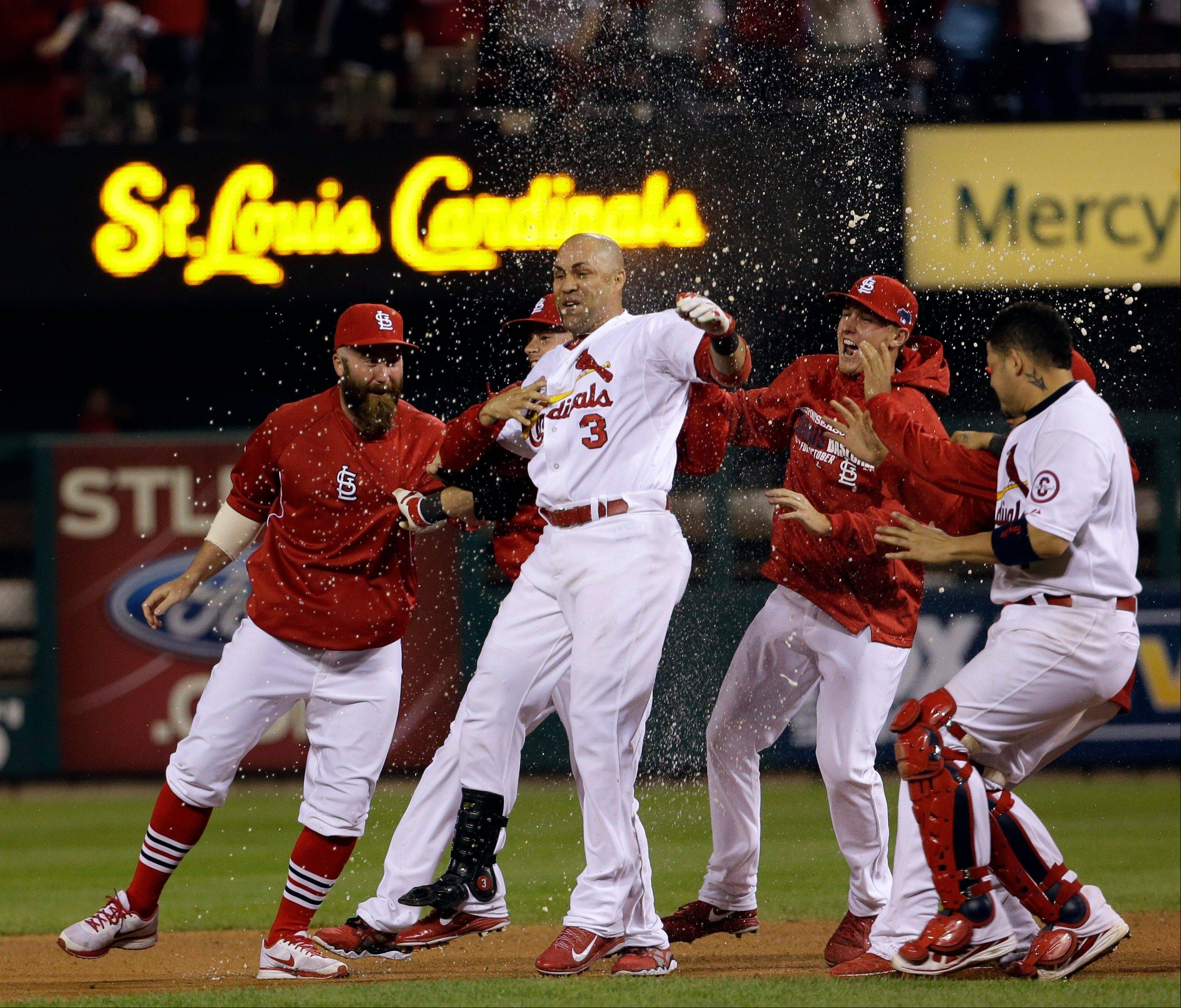 The Cardinals swarm Carlos Beltran after his game-winning hit during the 13th inning of Game 1 of the National League Championship Series against the Los Angeles Dodgers in St. Louis.