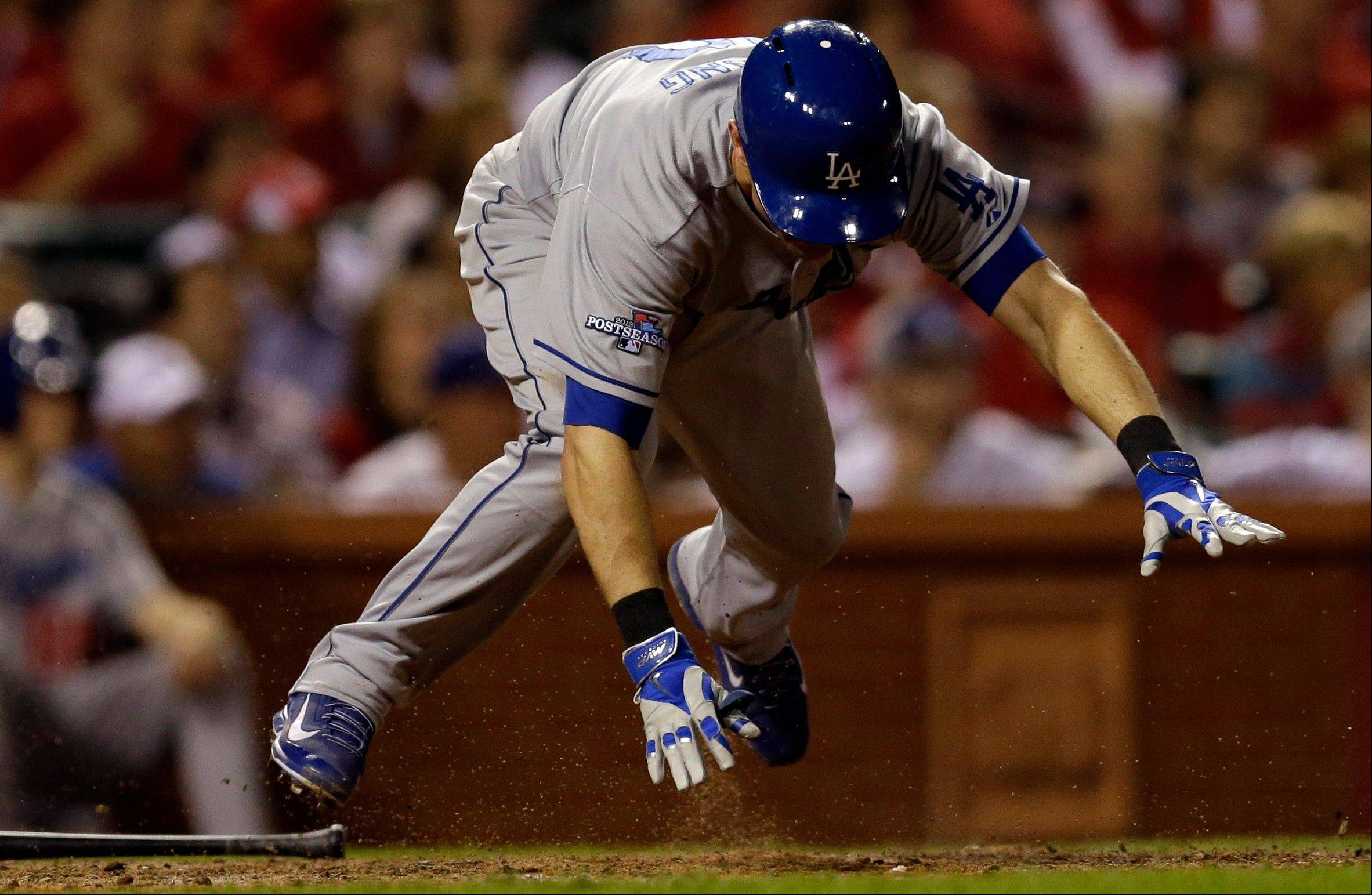 The Dodgers' Michael Young trips as he grounds into a double play during the 12th inning.