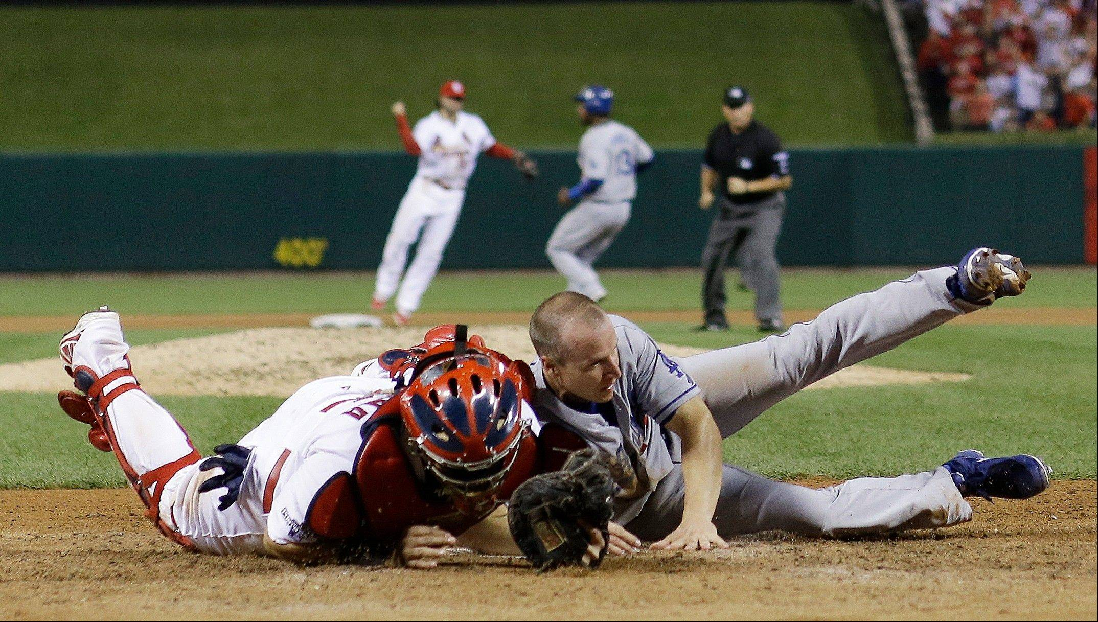 Cardinals catcher Yadier Molina tags out the Dodgers' Mark Ellis at home for the third out in the 10th inning.