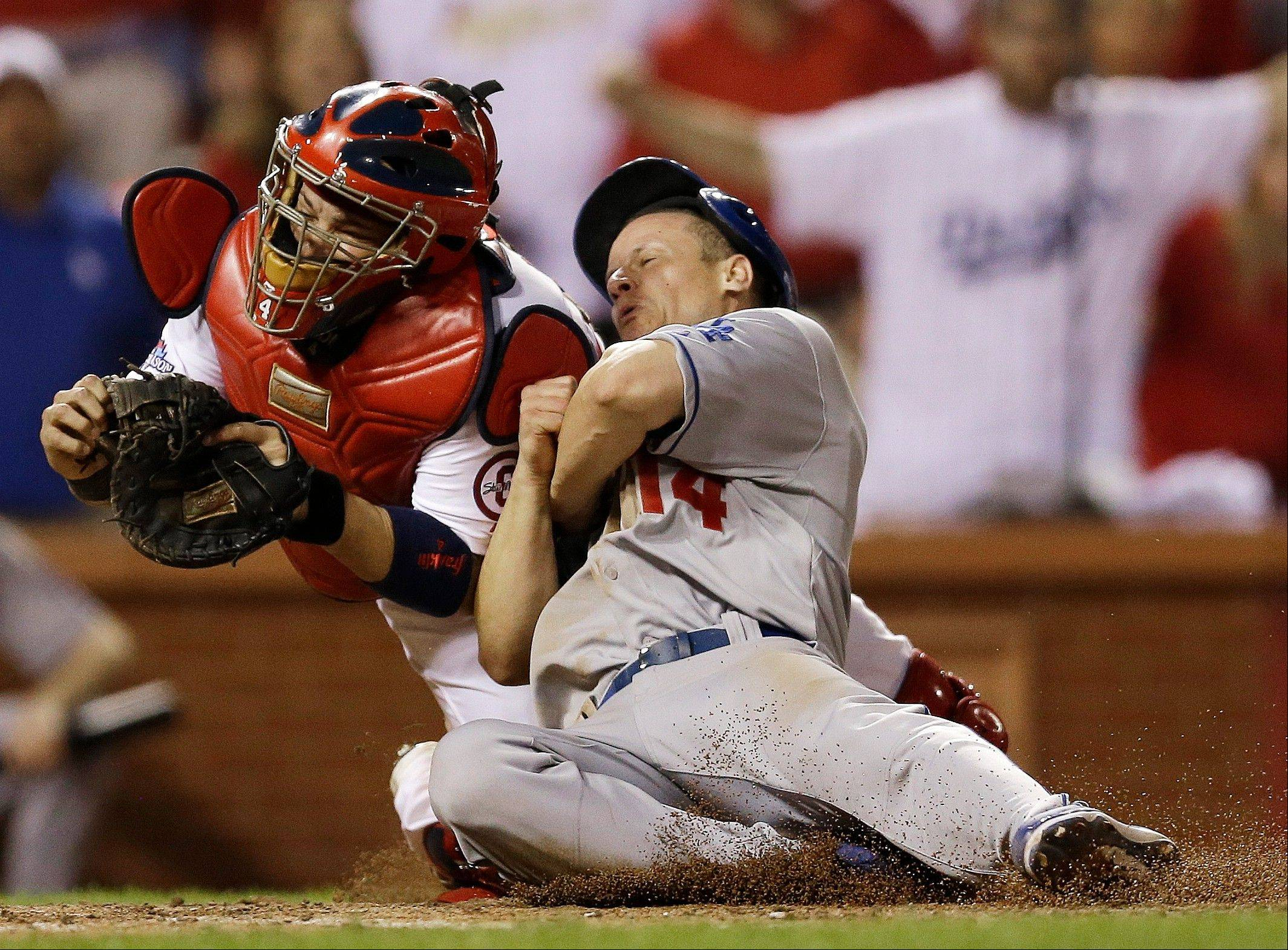 The Dodgers' Mark Ellis barrels into Cardinals catcher Yadier Molina in the 10th inning.